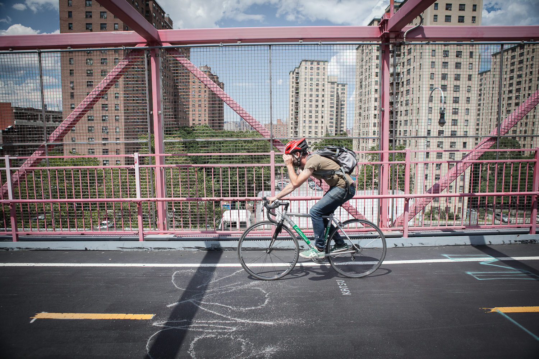 Man riding his bike on the Williamsburg Bridge, New York