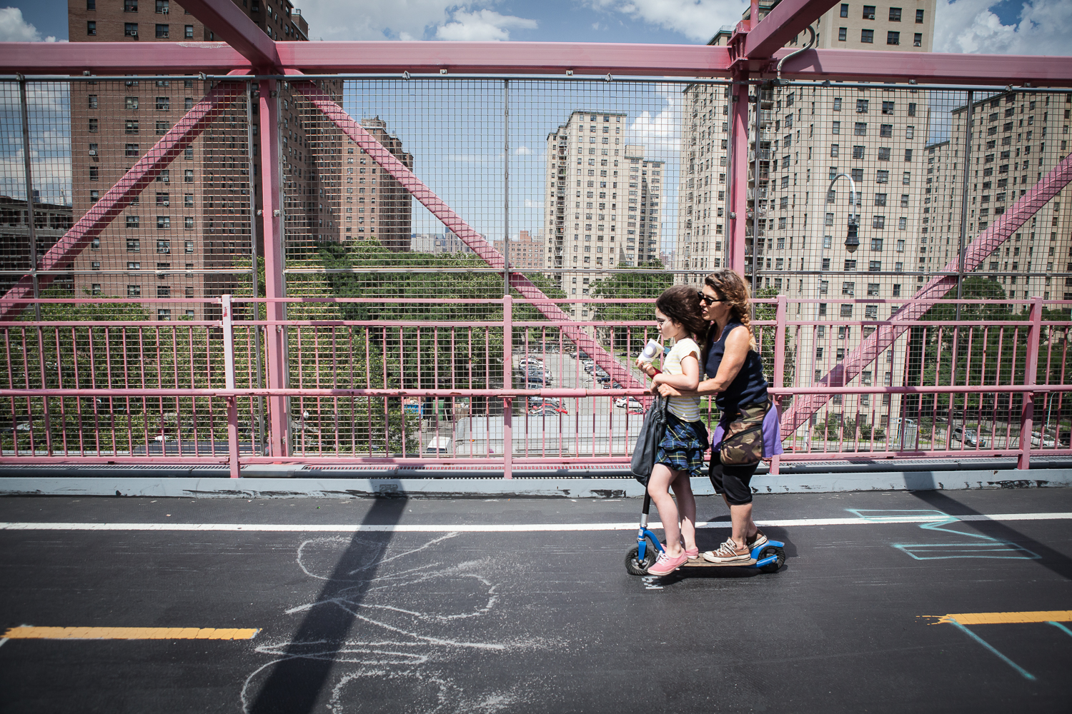 Mother and daughter riding their scooter on the Williamsburg Bridge, New York
