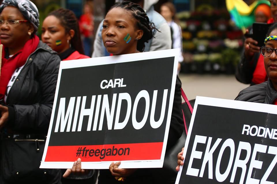 Femme gabonaise brandissant sur une pancarte le nom d'un prisonnier politique.