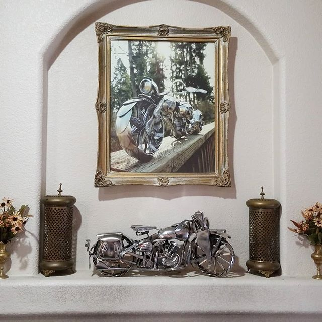 "Sometimes our photos make the spoon motorcycle sculptures look life size. For some perspective, here is ""The Liberator"" on our mantle. It is a 19 inch (48cm) interpretation of the WLA Harley, used in WWII. The fine details, including the Thompson submachine gun, are all made with stainless steel spoons welded together.  #JamesRice #FineArt #motorcycleart #metalart #HarleyDavidson #HD #EverlastingSpoonful #art #SpoonMotorcycle"