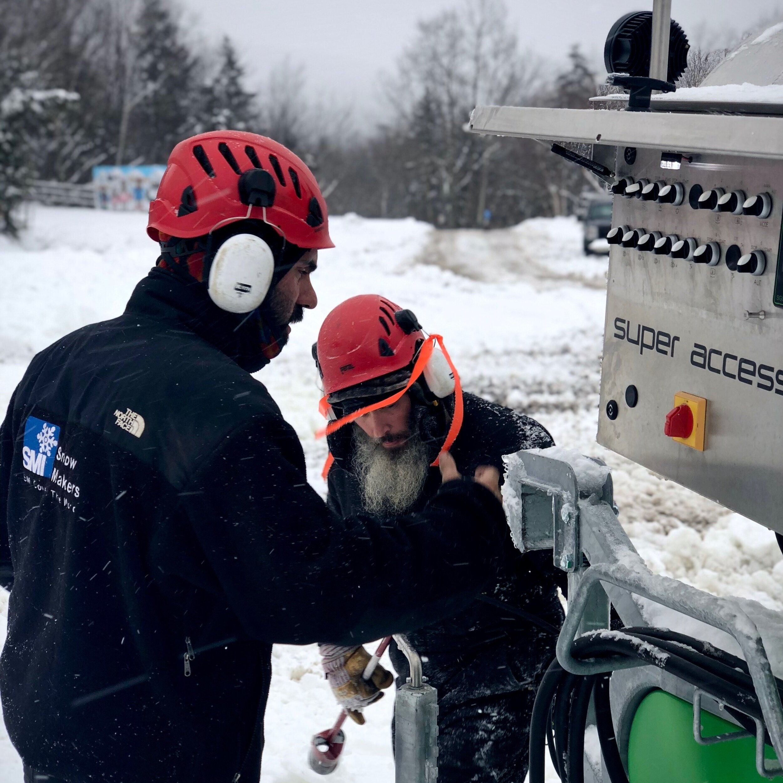 Snowmakers making adjustments on the control panel.