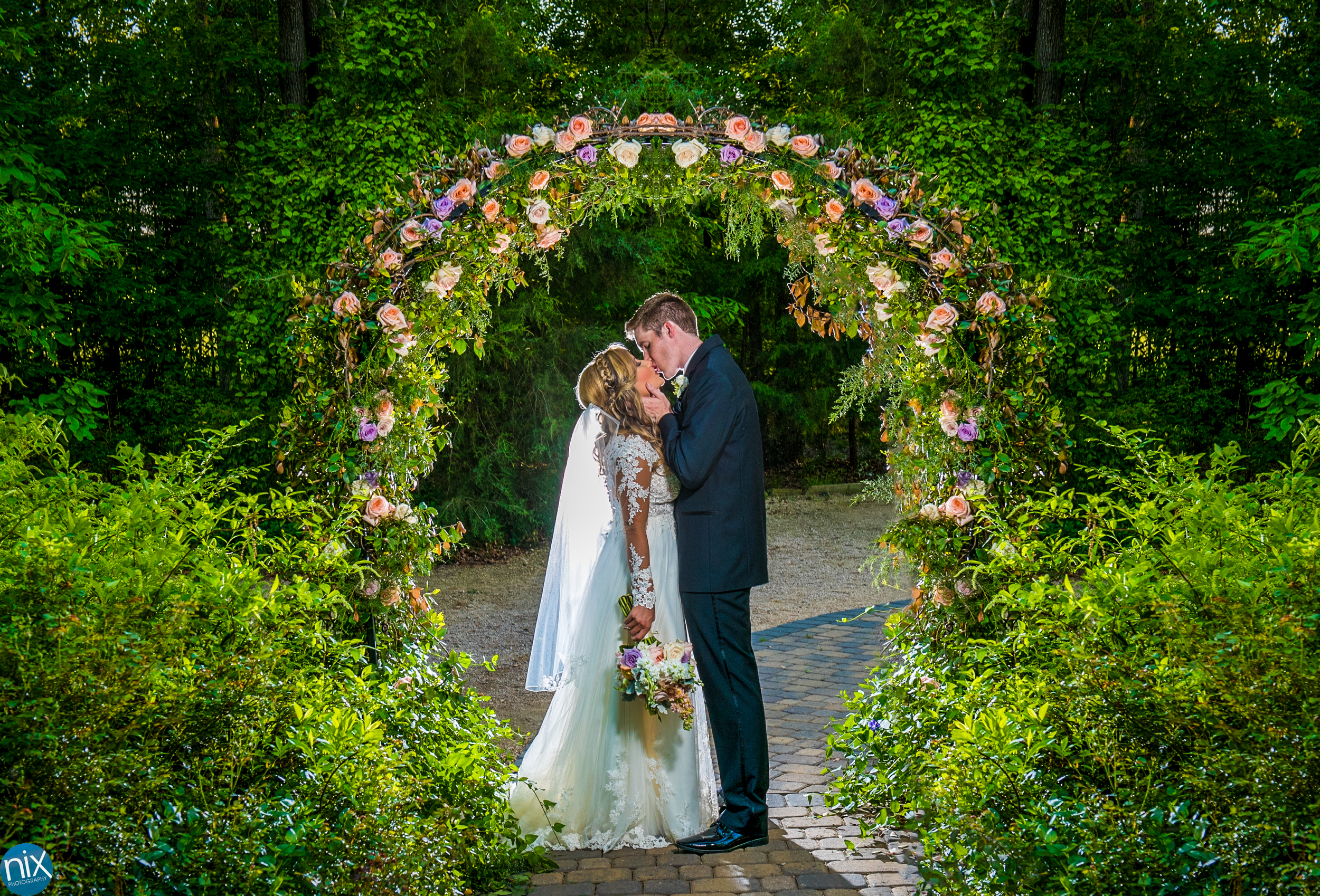 bride and groom kiss under flower arch Morning Glory Farm.jpg