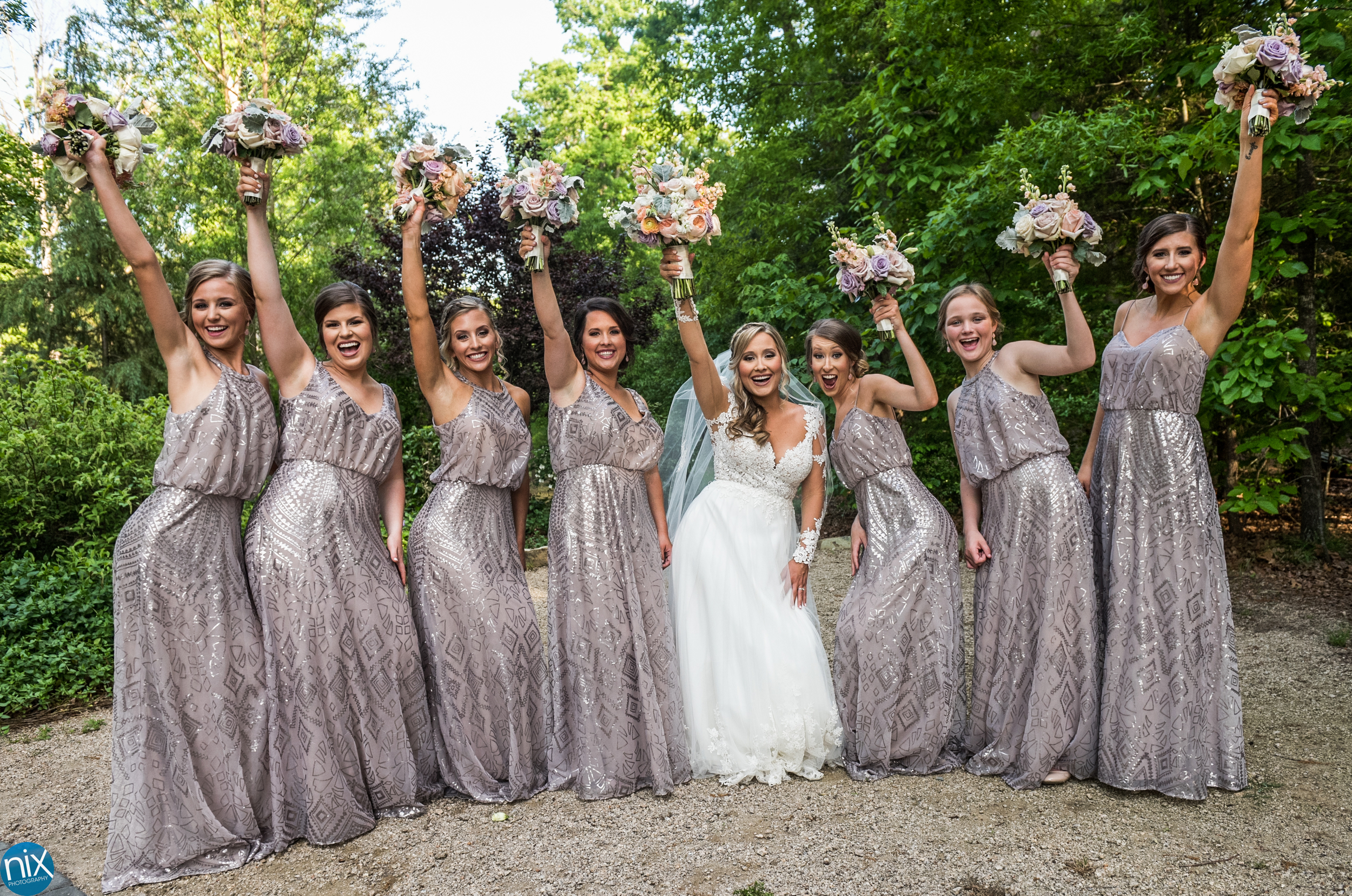 bride and bridesmaids hold up bouquets .jpg