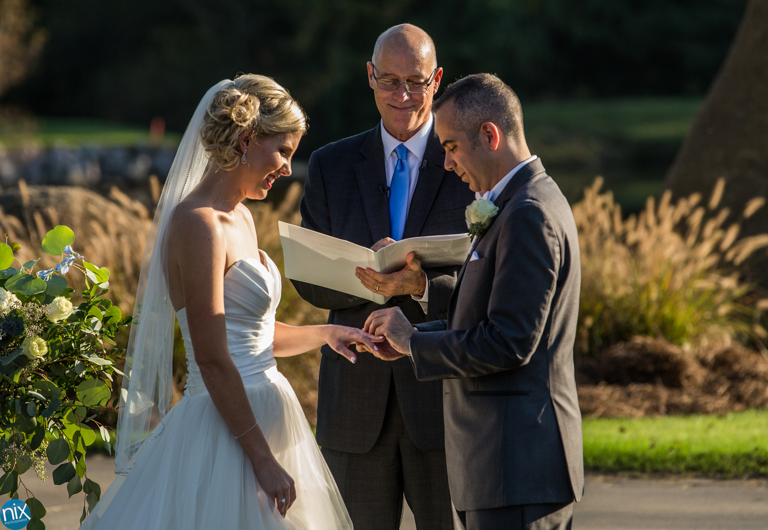 groom puts rung on brides finger at North Stone Country Club in Huntersville.jpg