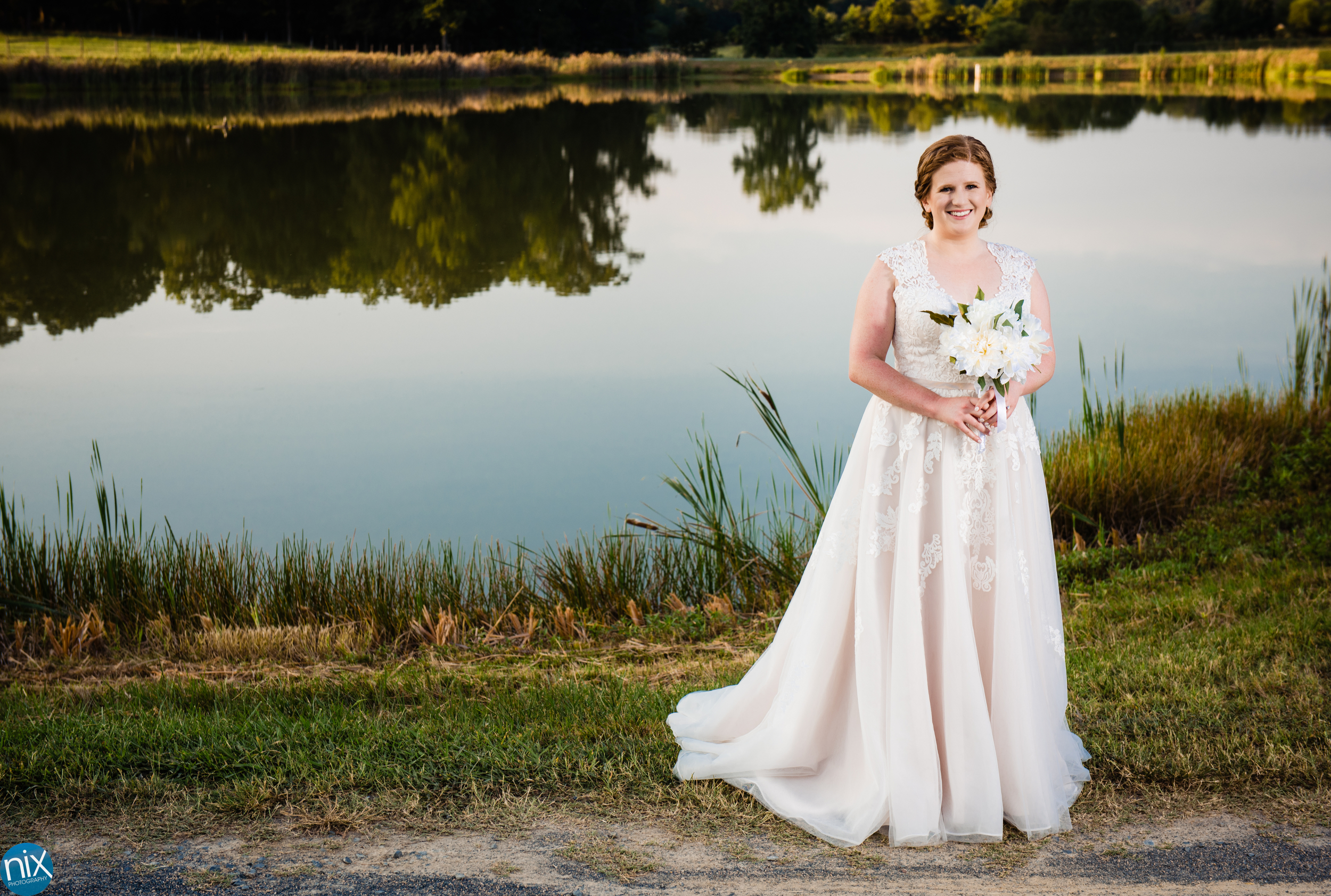 bride in wedding dress in front of a pond.jpg