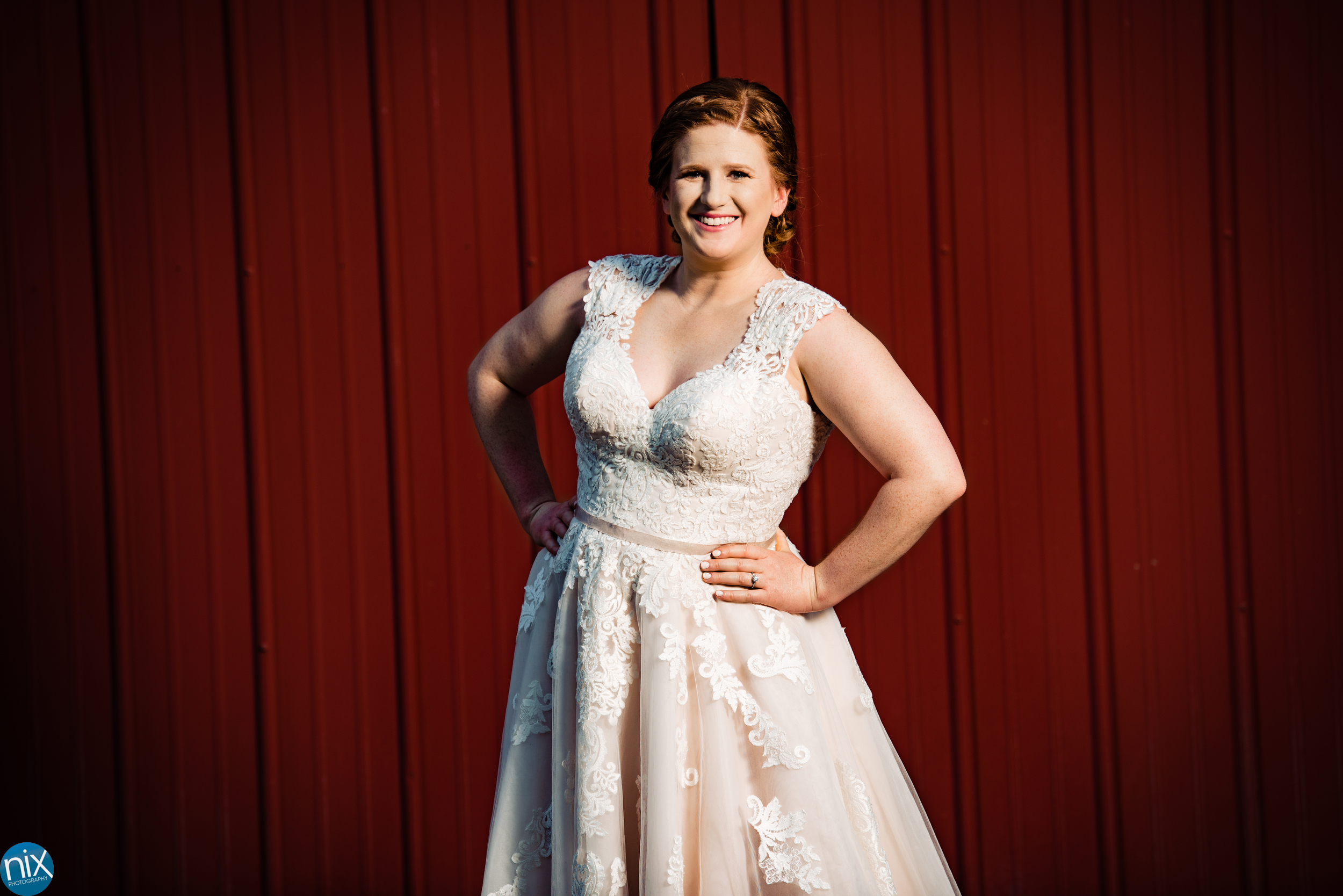 bride in wedding dress with red barn.jpg