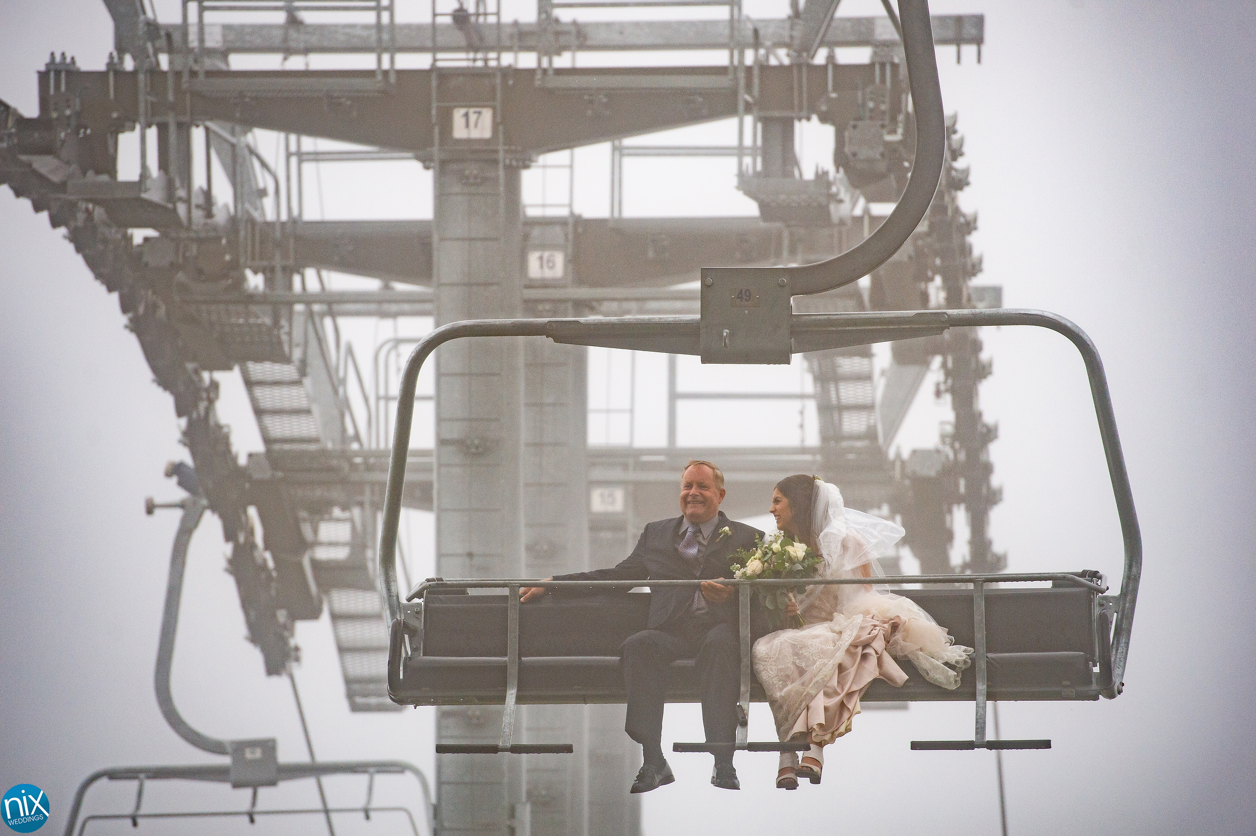 bride and father ride ski lift to wedding ceremony.jpg
