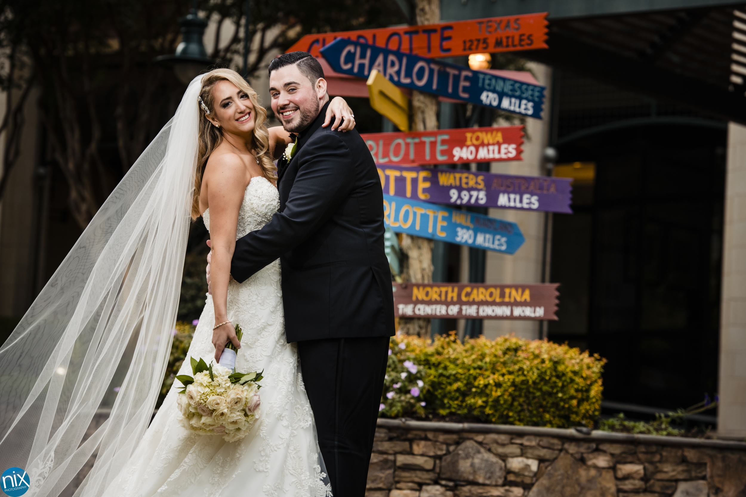 bride and groom at the green in charlotte with charlotte signs.jpg