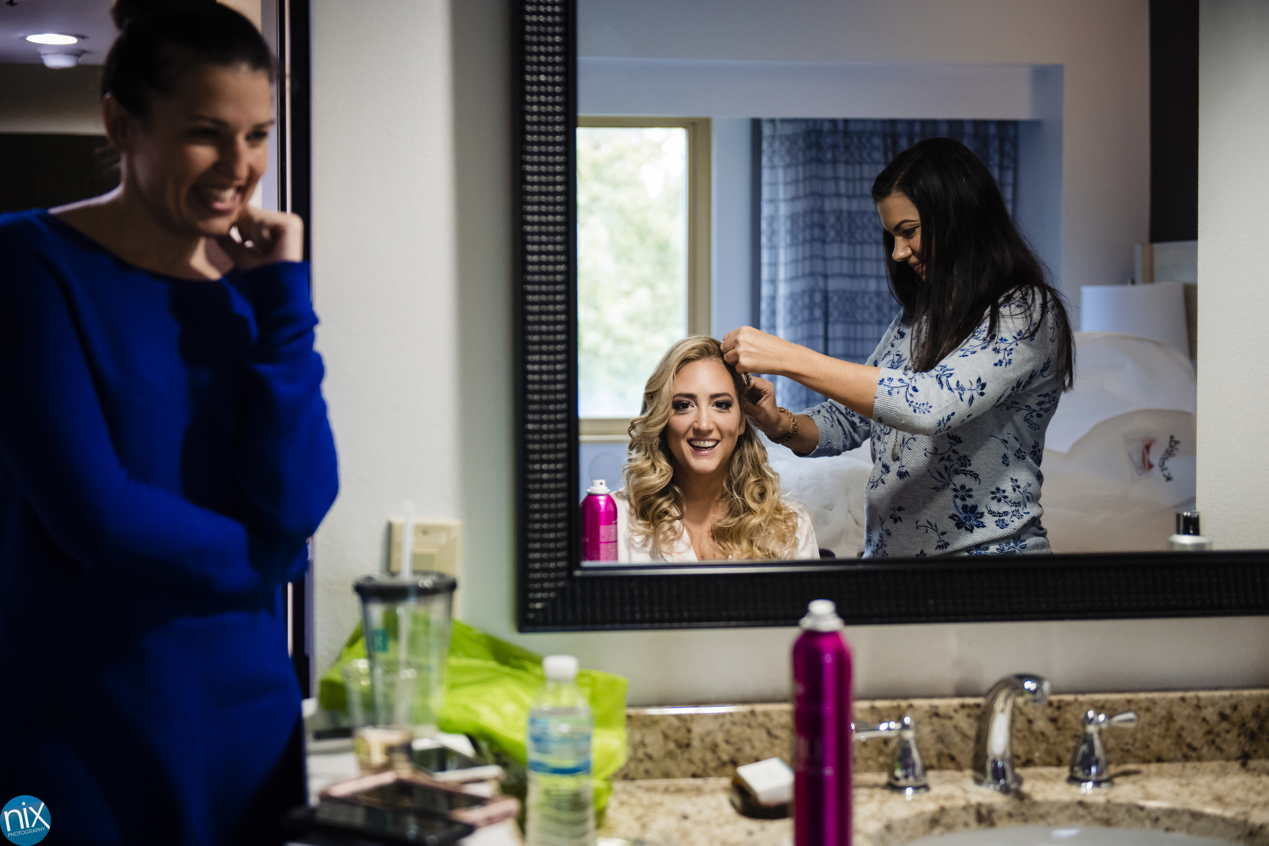 bride reflection as she gets ready at embassy suites charlotte.jpg