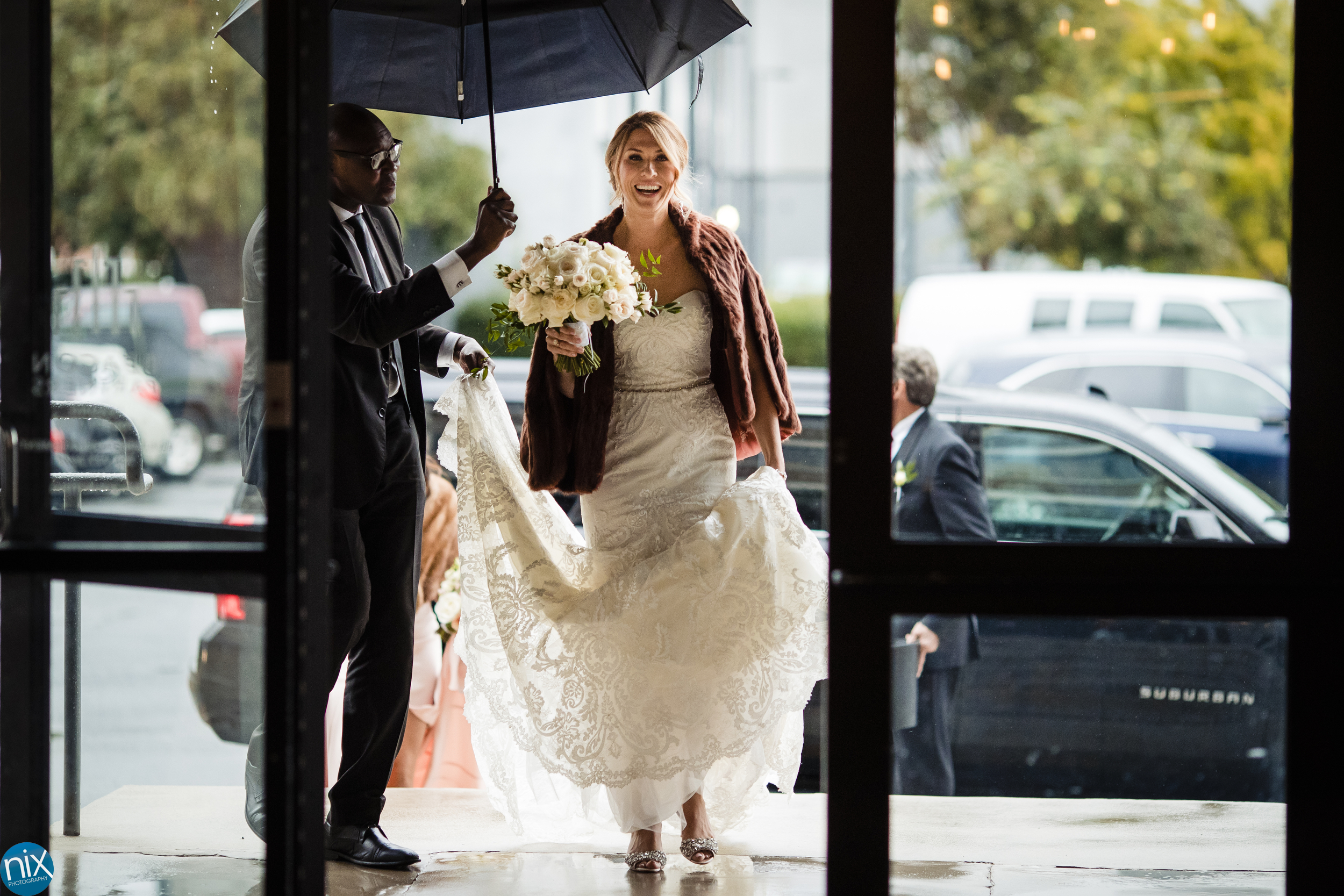 bride enters under an umbrella for a wedding at The Terrace at Cedar Hill.jpg