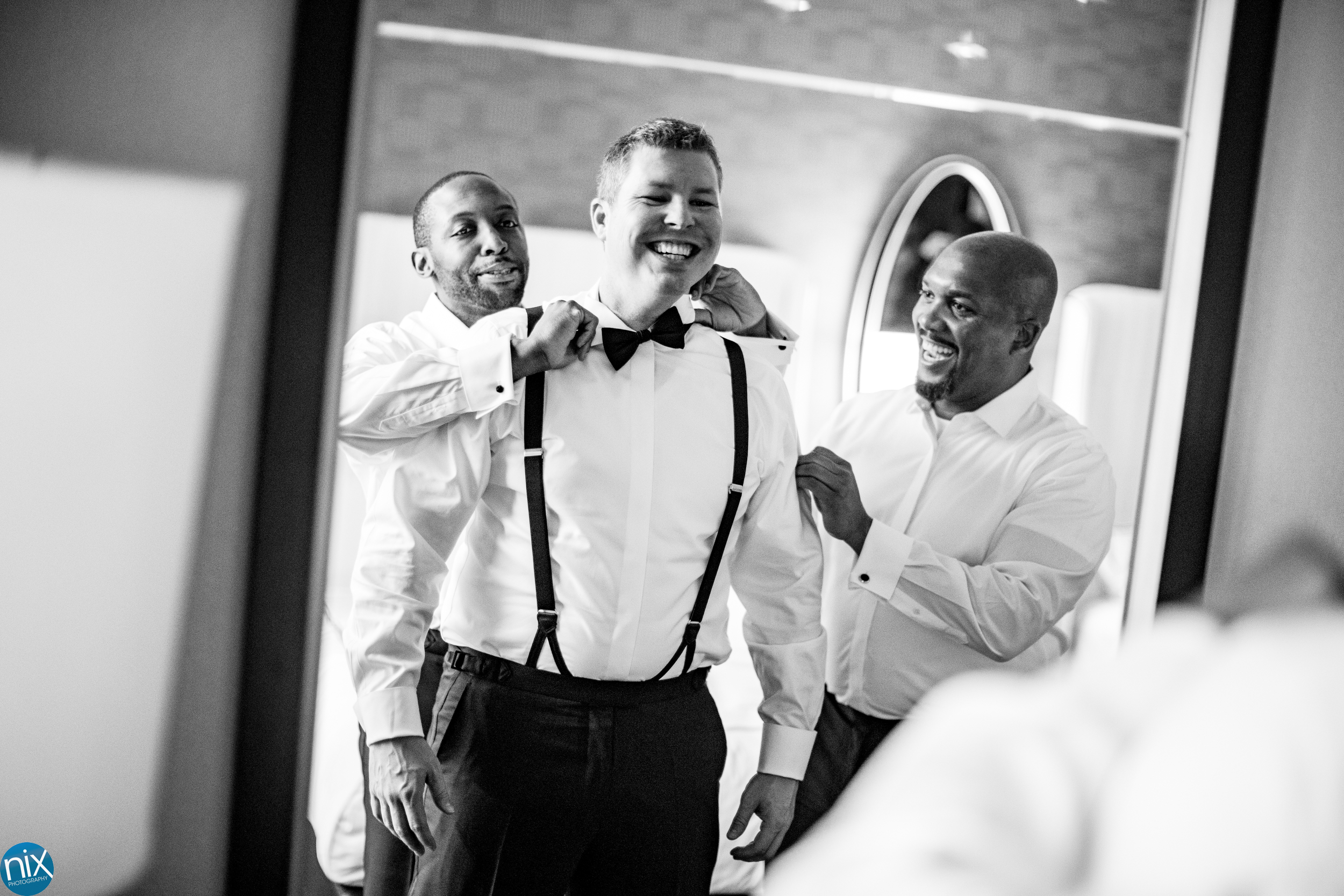 groom gets help from groomsmen before a wedding at Kimpton Tryon Park Hotel in Charlotte.jpg