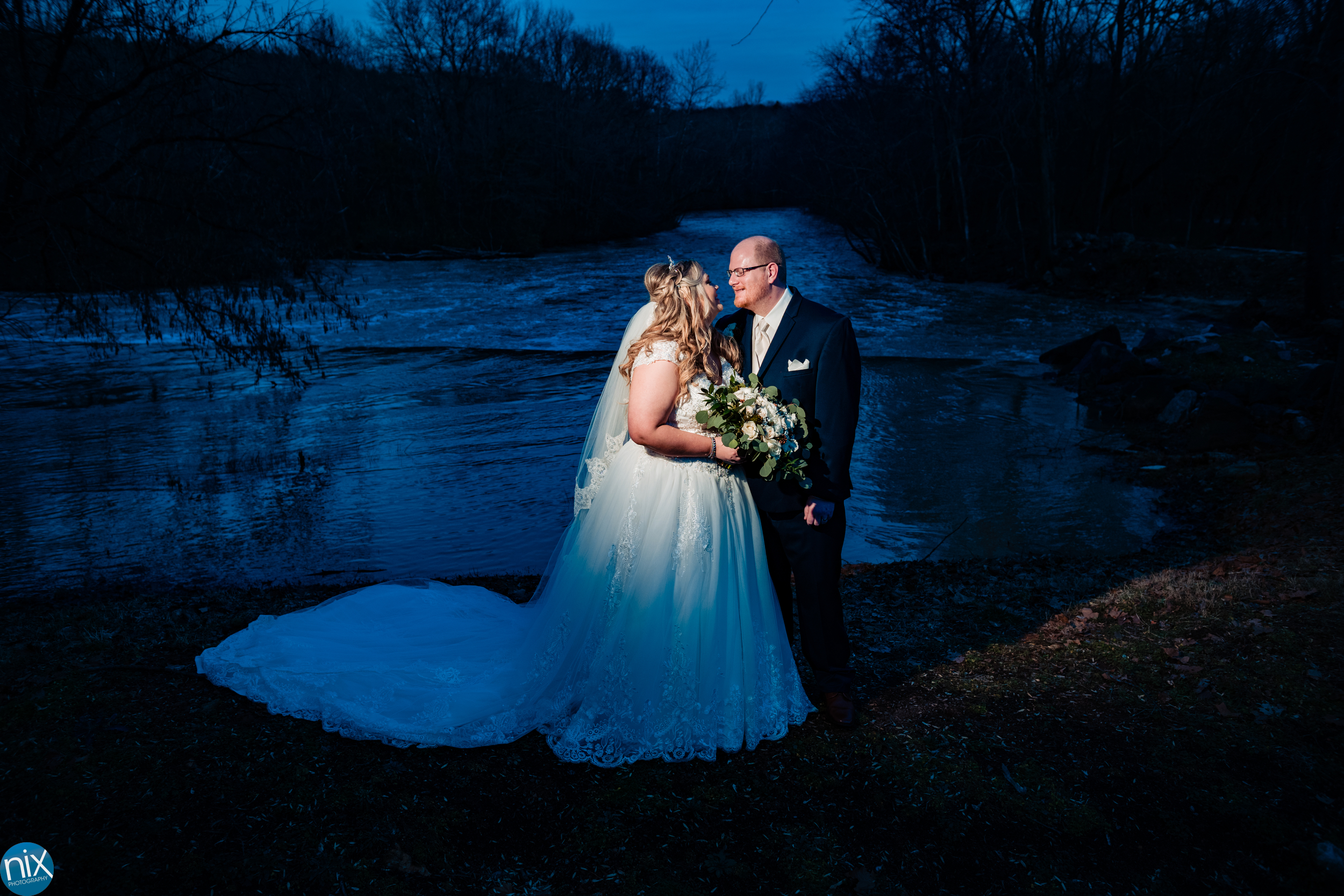 bride and groom by river at Laboratory Mills .jpg