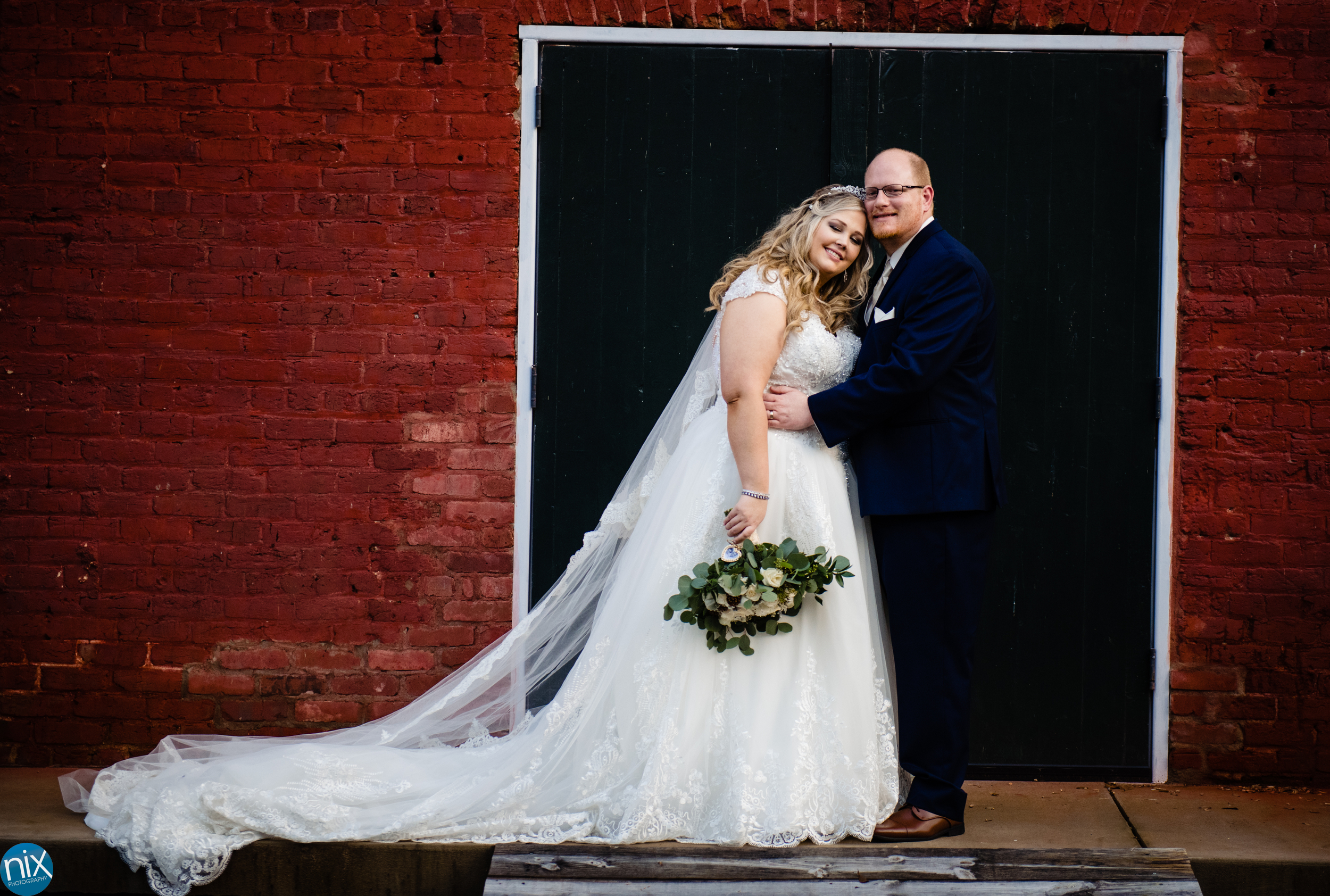 bride and groom in front of red wall at Laboratory Mills.jpg