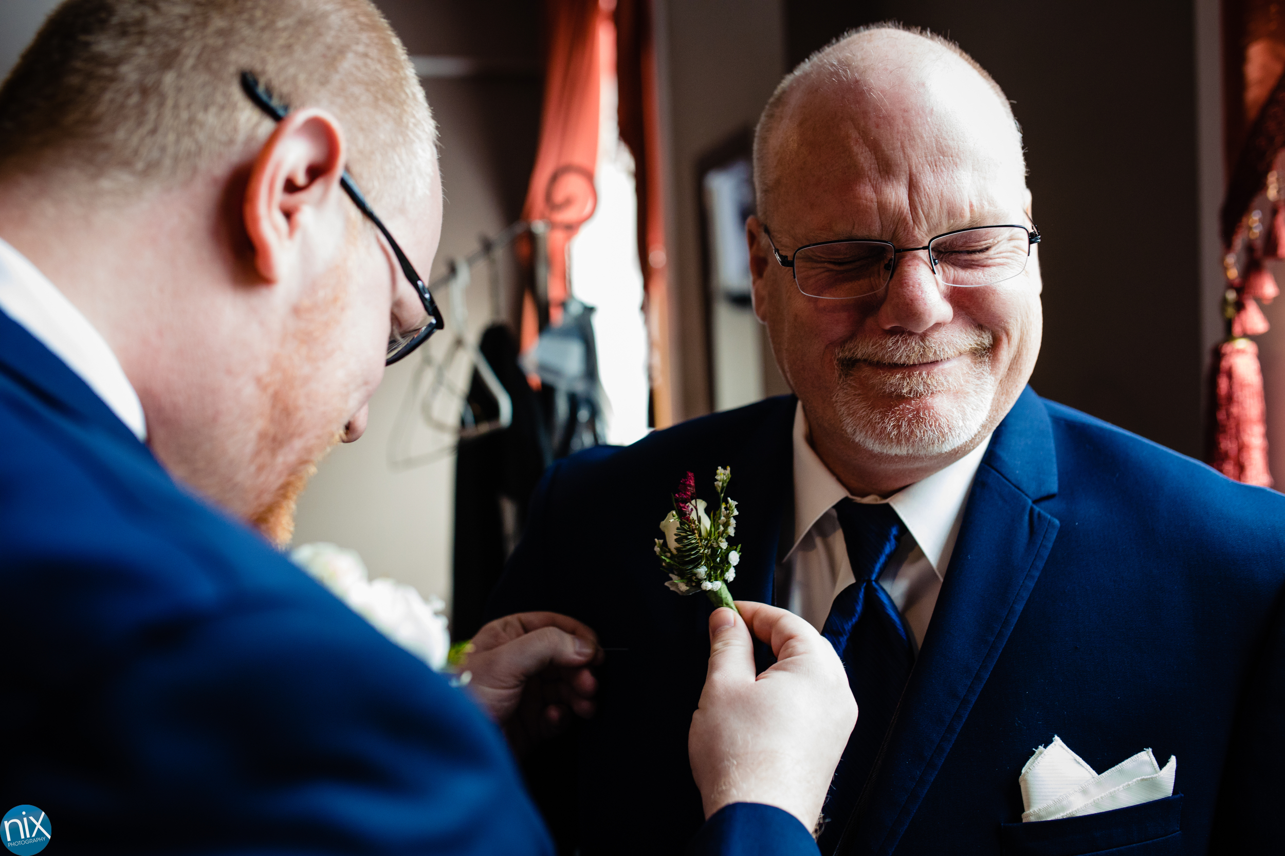 dad cries ar son places boutonniere on jacket.jpg