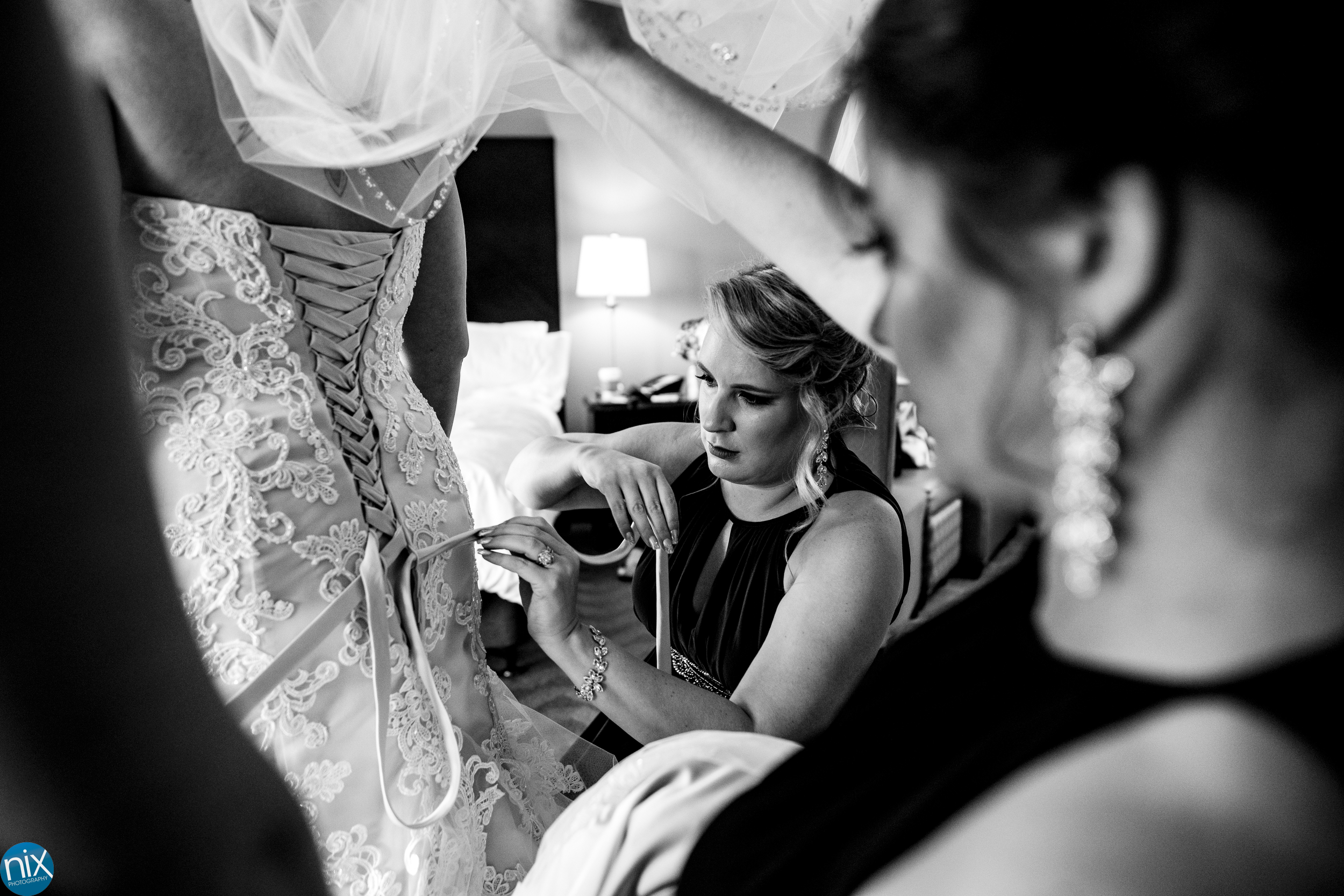 bridesmaids help bride get into dress at Holiday Inn Rock Hill.jpg