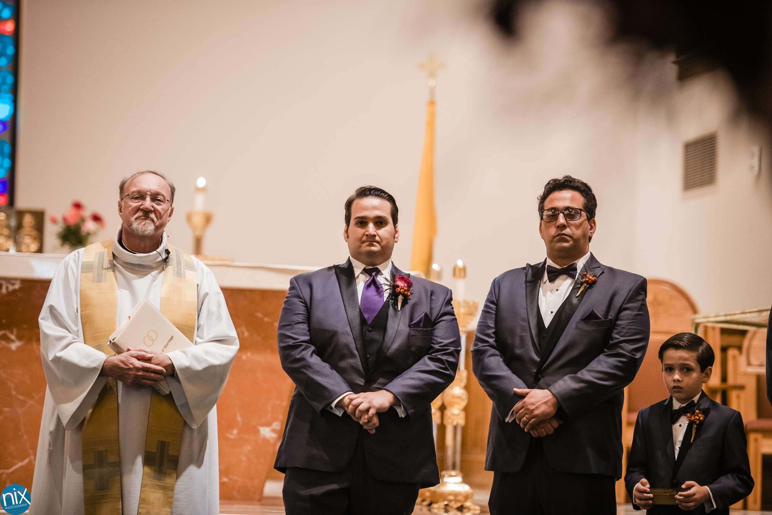 groom watches bride during wedding ceremony at St Philip Neri Catholic Church.jpg