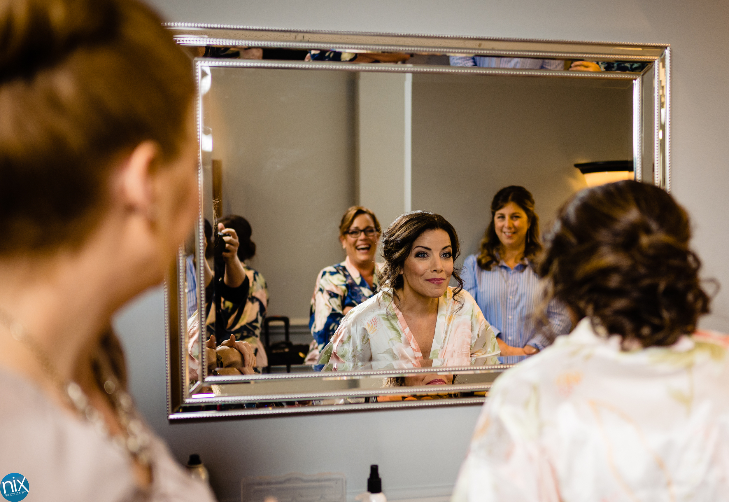 bride looks in mirror to see her makeup