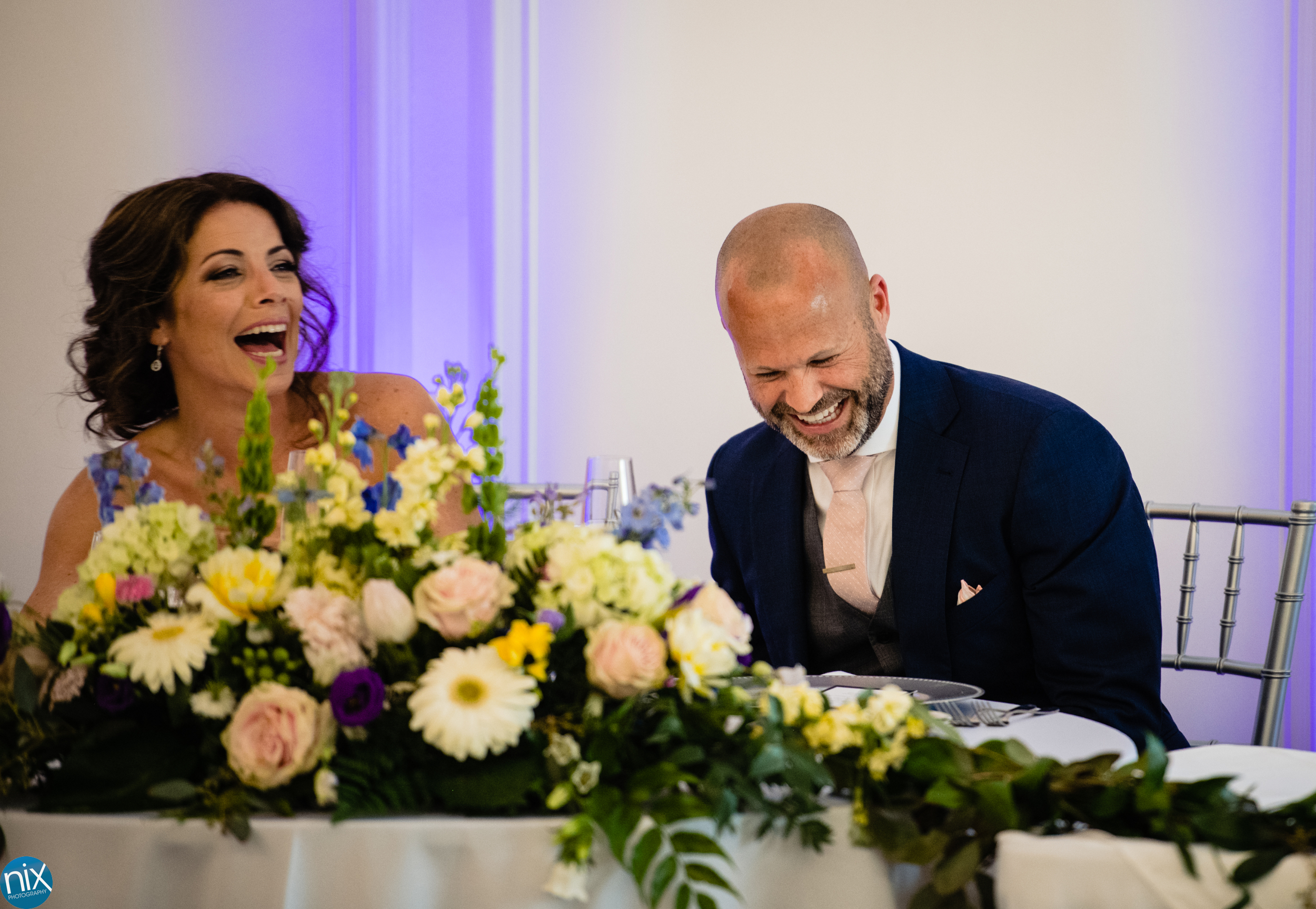 groom and bride laugh during toast