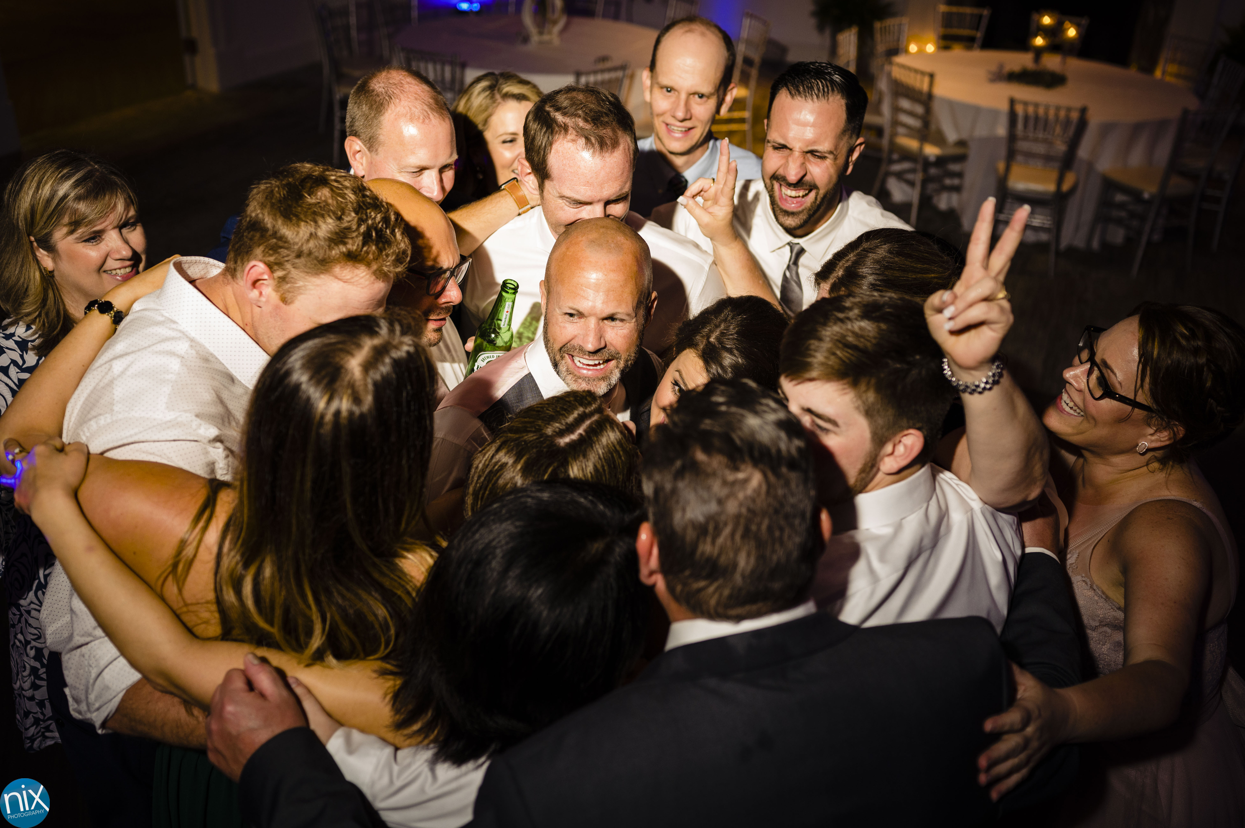 groom surrounded by friends at wedding reception