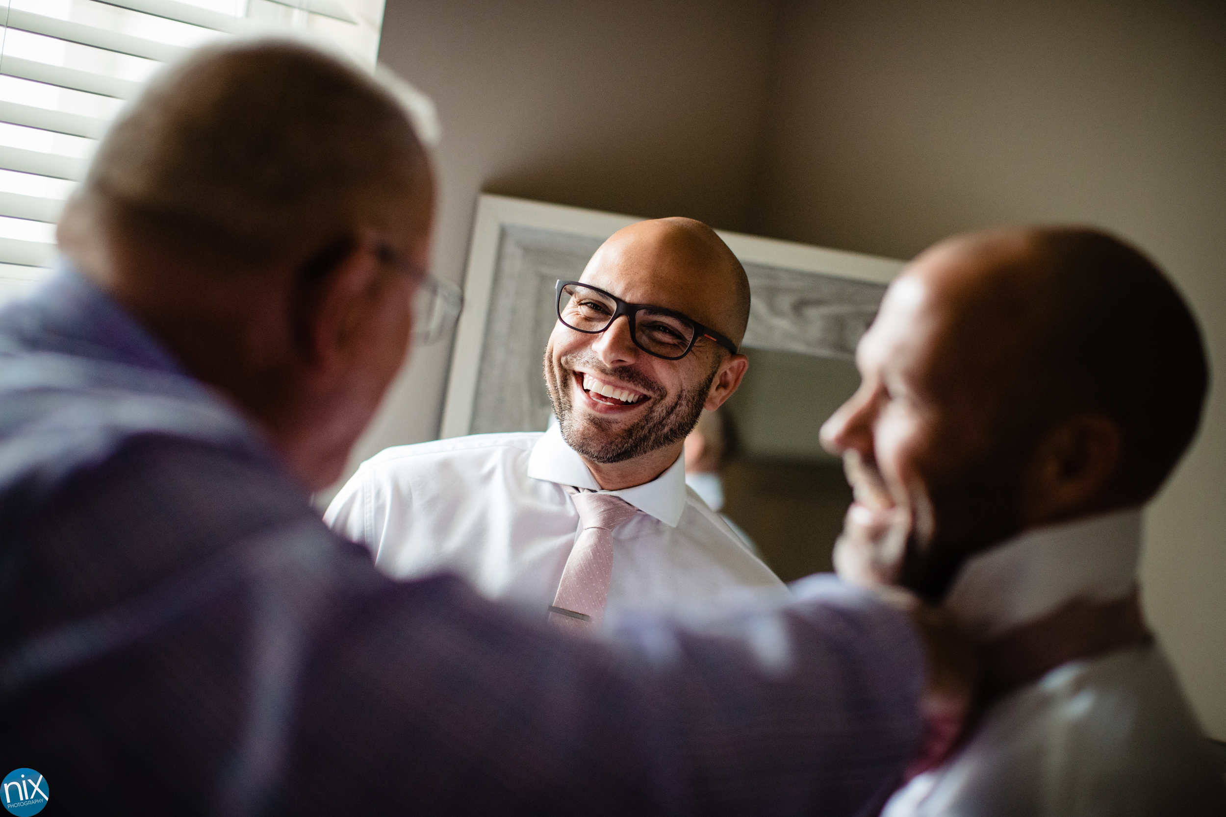 groomsman laughs as groom gets ready for wedding
