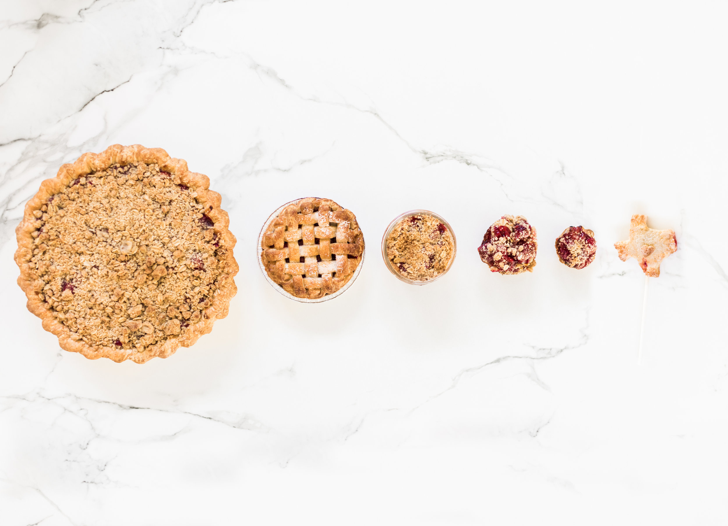 "Happiness comes in all different sizes .  From left : Not So Tiny Pie, 5"" Pie, Mason Jar Pie, Traditional Tiny Pie, Teeny Tiny Pie, Pie Pop."