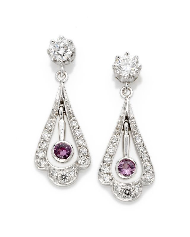 Chandelier white gold earrings with two claw-set diamonds, graduated grain-set diamonds and two bezel-set pink sapphires.