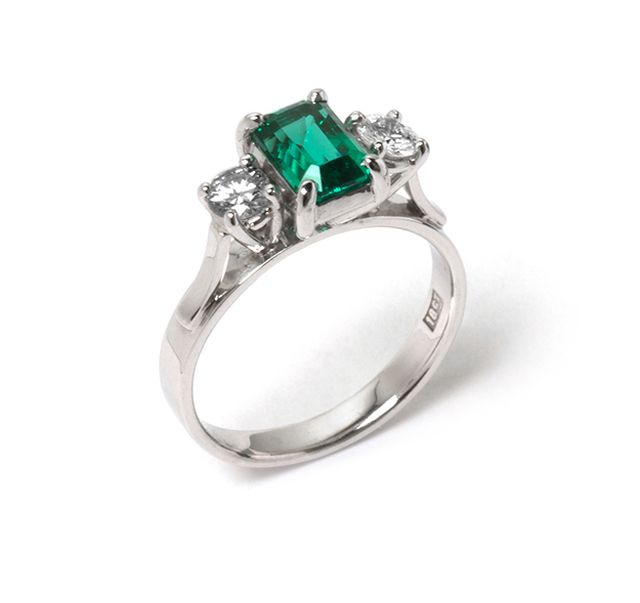 White gold ring with claw-set emerald and two claw-set round diamonds in white gold.