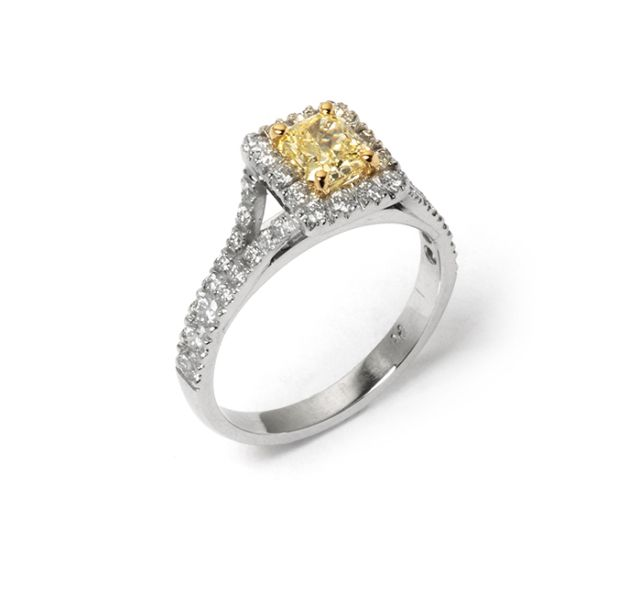 Fancy yellow diamond claw-set in yellow gold with micro-set diamond halo and shoulders in white gold.