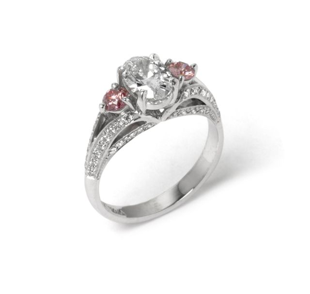 Pink diamonds claw-set either side of centre diamond with grain-set diamond shoulders and band.