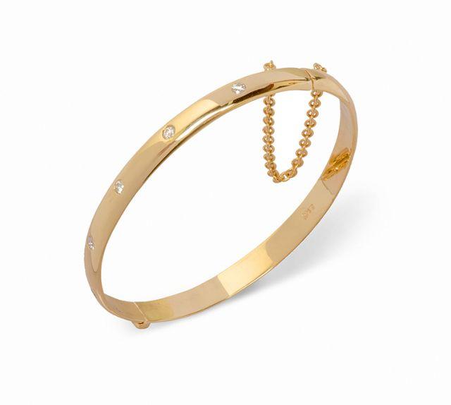 Yellow gold hinged bangle with gypsy-set diamonds.