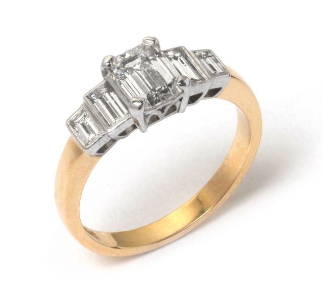 Art deco inspired yellow and white gold diamond set ring. Claw set center stone with two diamonds bezel-set either side.