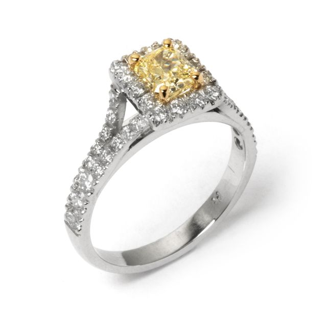 Fancy-yellow diamond ring claw-set in yellow gold with white gold diamond set halo and shoulders.