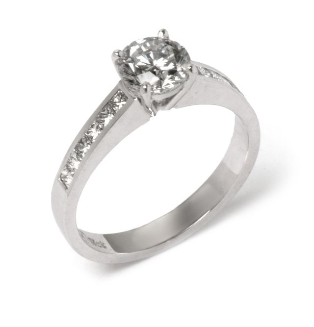 4 claw Diamond set ring in white gold with channel-set Diamond shoulders