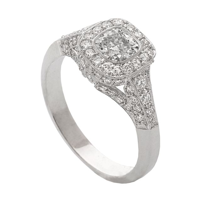 Art deco style cushion cut Diamond ring with grain-set Diamond halo, rails and shoulders. All in white gold