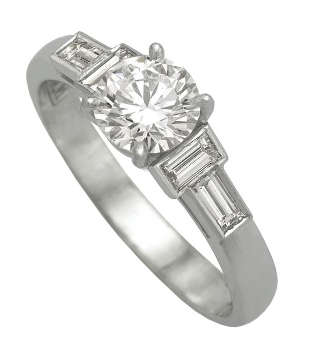 White gold ring with claw-set centre stone and two baguette cut diamonds bezel-set either side.