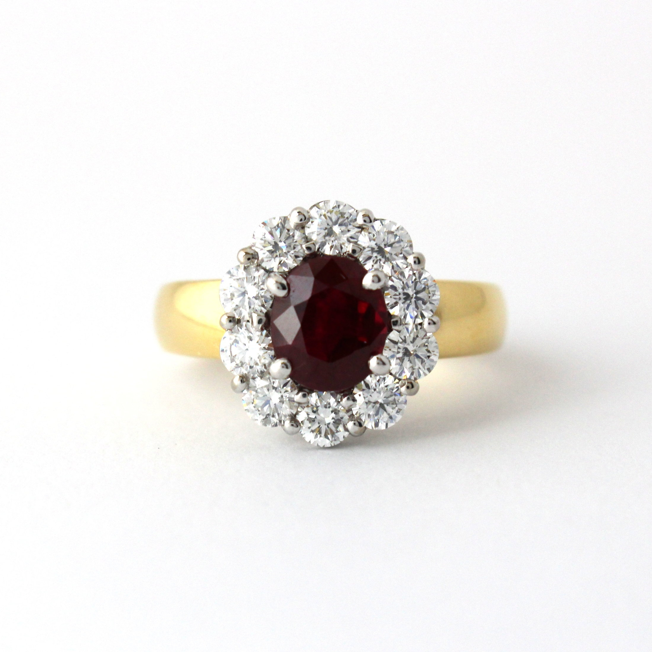 Ruby with diamond halo in yellow and white gold ring.