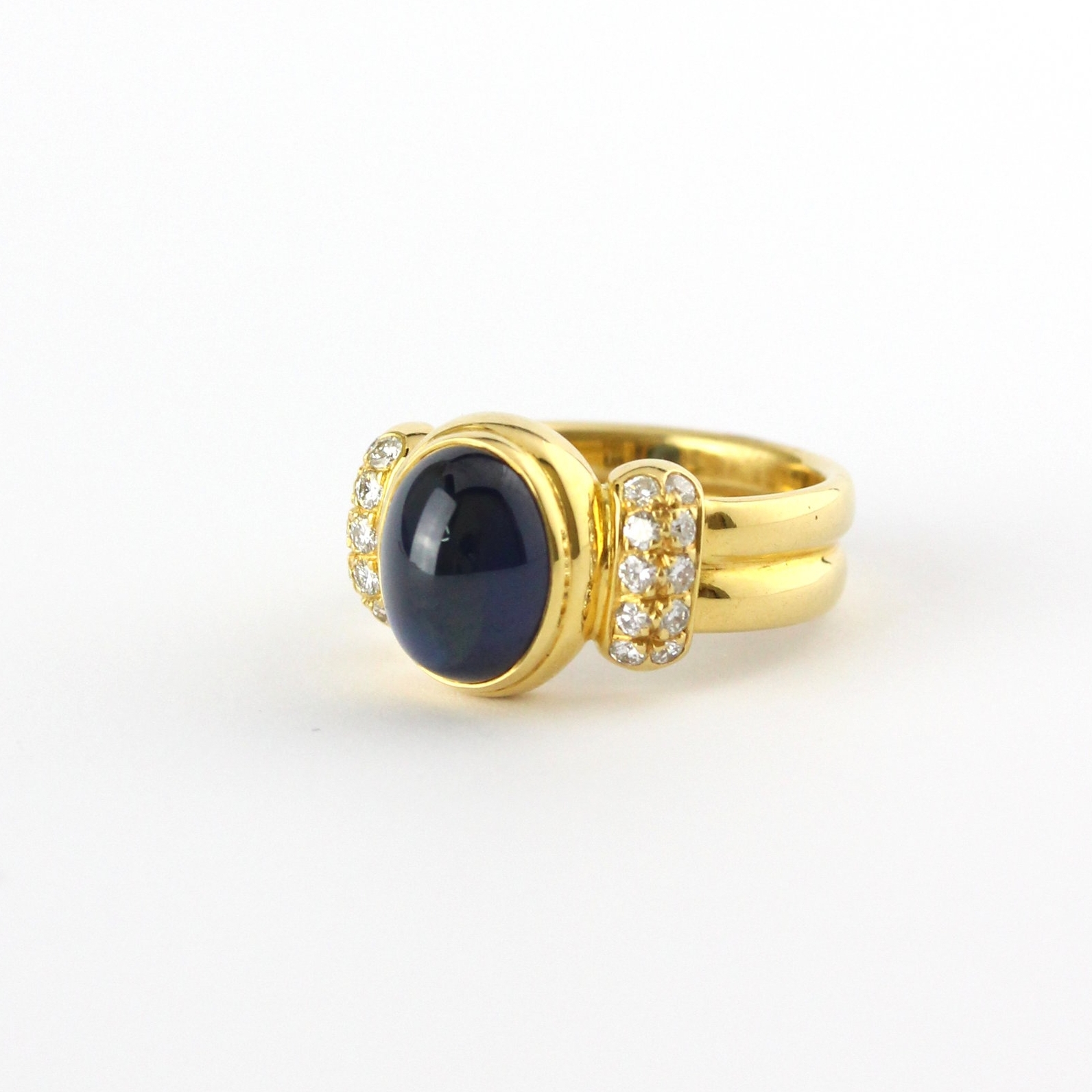 Cabochon sapphire ring with diamond shoulders set in yellow gold.