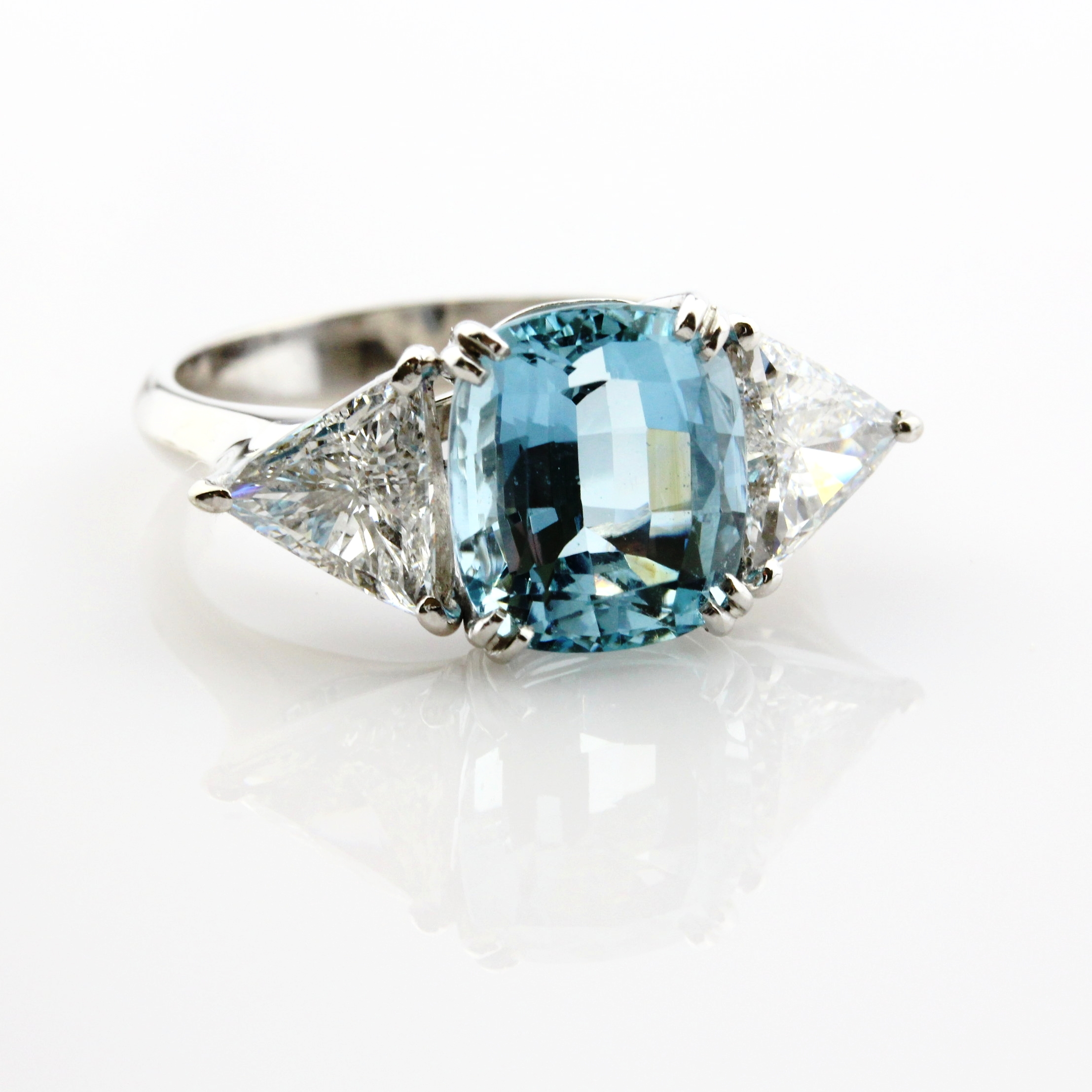 White gold ring with double-claw set cushion cut aquamarine with trillion cut diamonds.