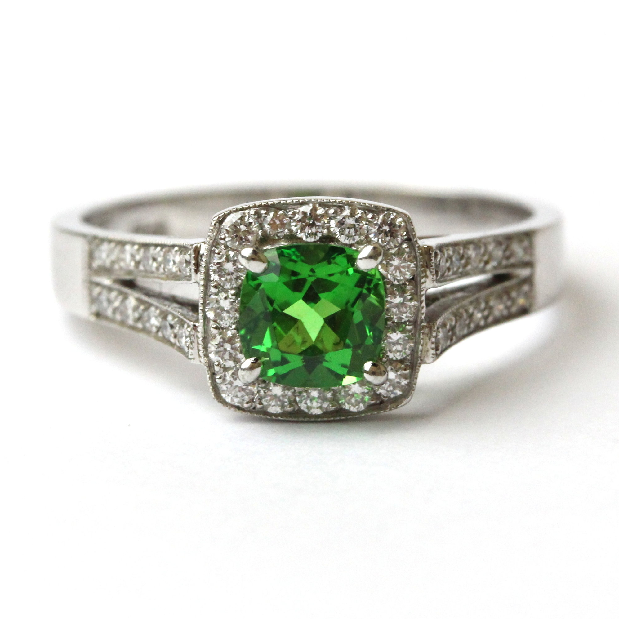 Cushion cut tsavorite garnet set in white gold ring with diamond halo and shoulders.