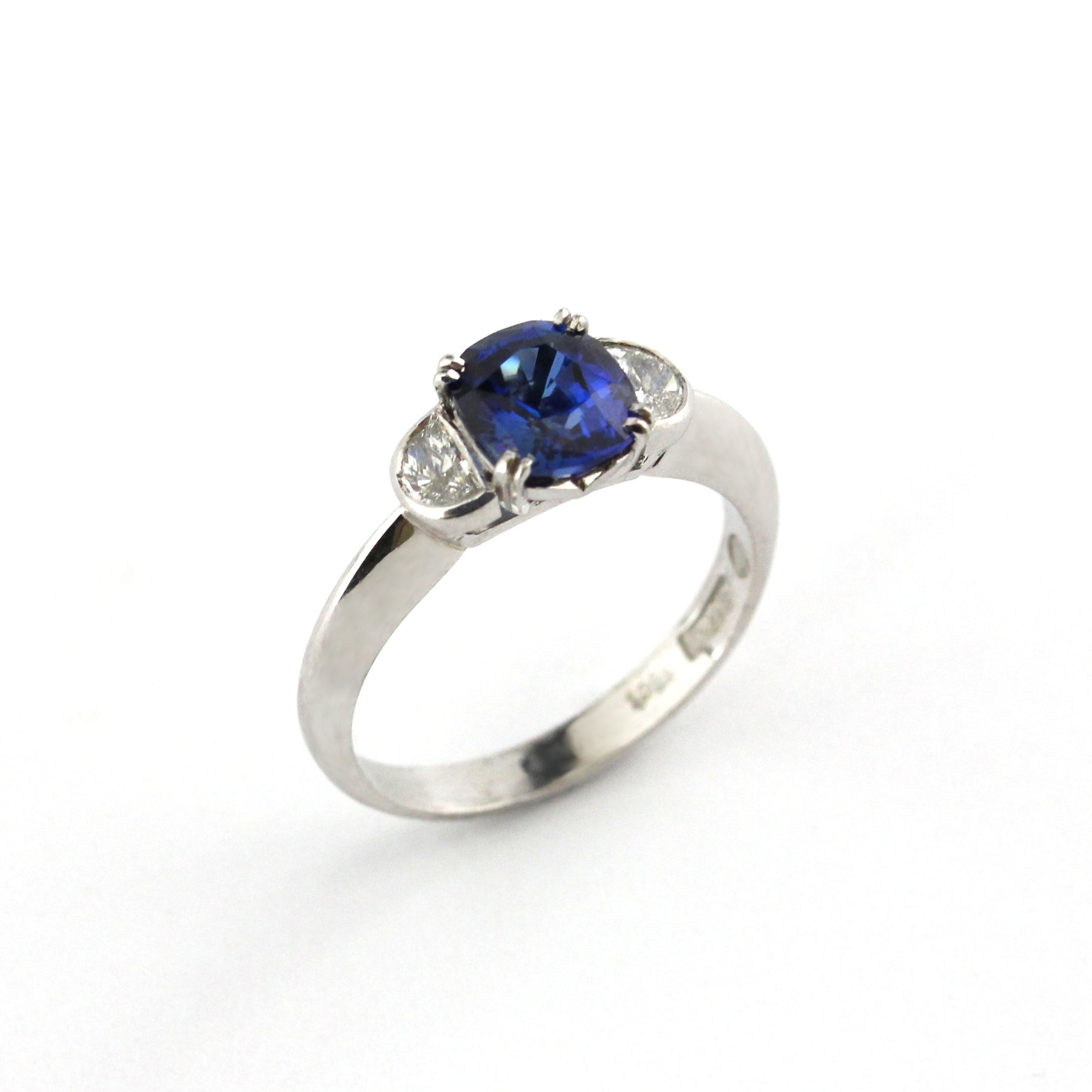 Double claw set sapphire white gold ring with crescent diamond bezel set shoulders.
