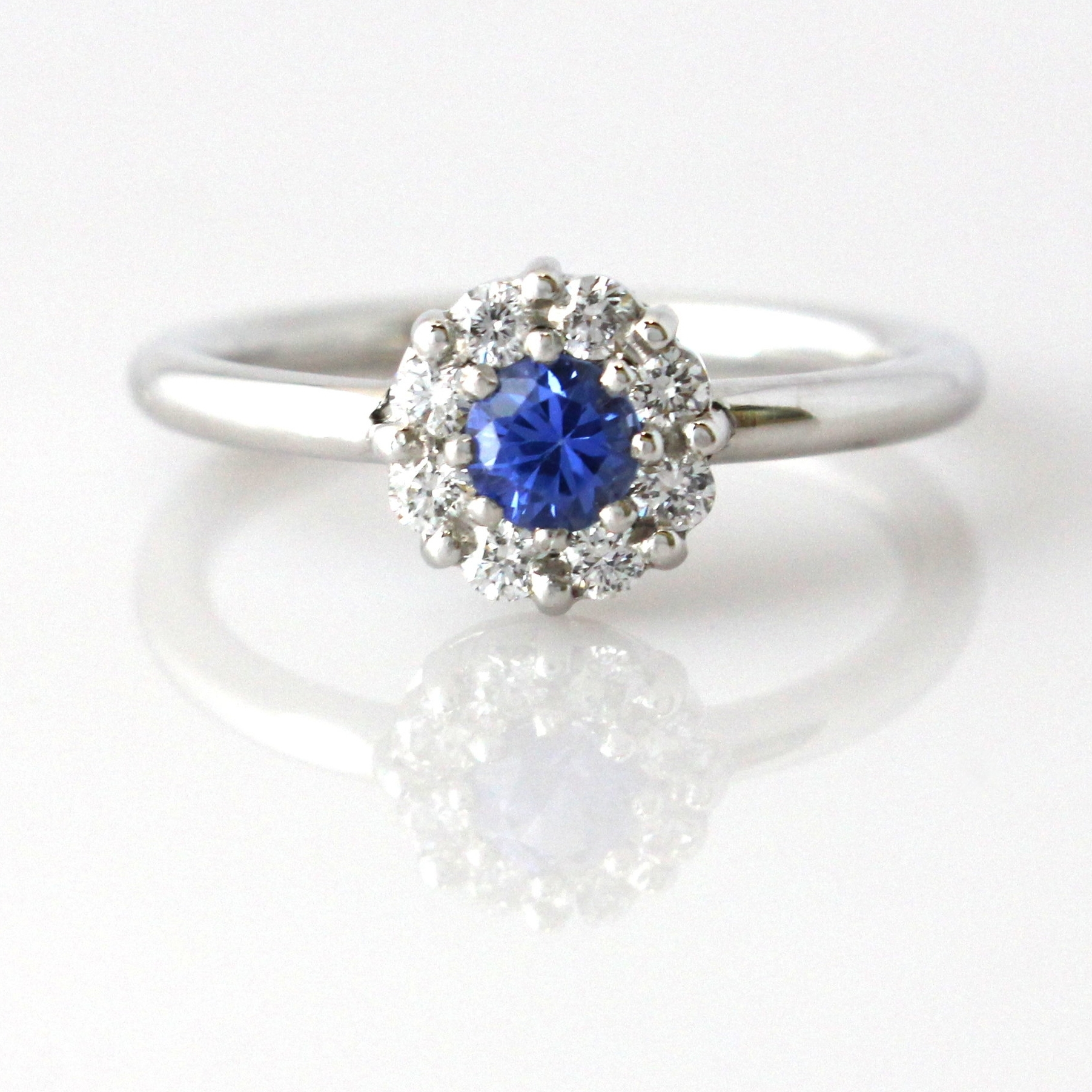 Ceylon sapphire with diamond cluster set in white gold ring.