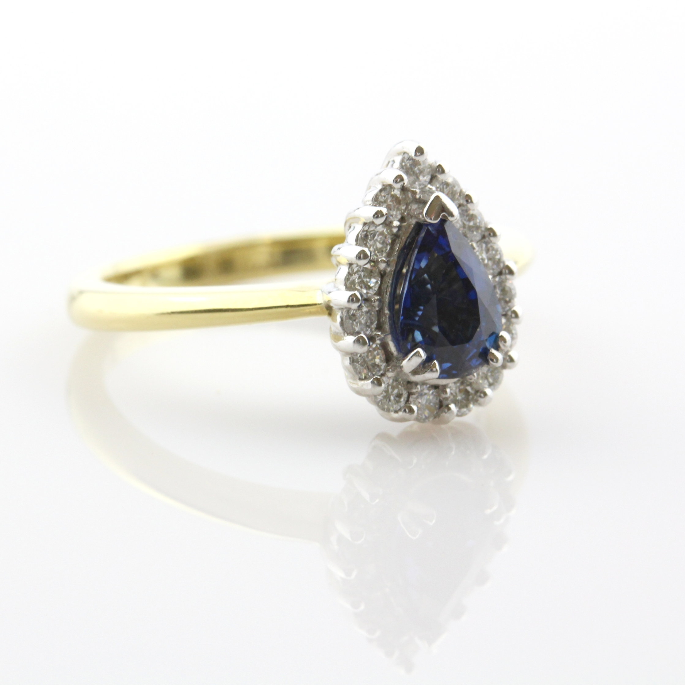 Double claw set pear shaped ceylon sapphire with diamond cluster in white gold ring.