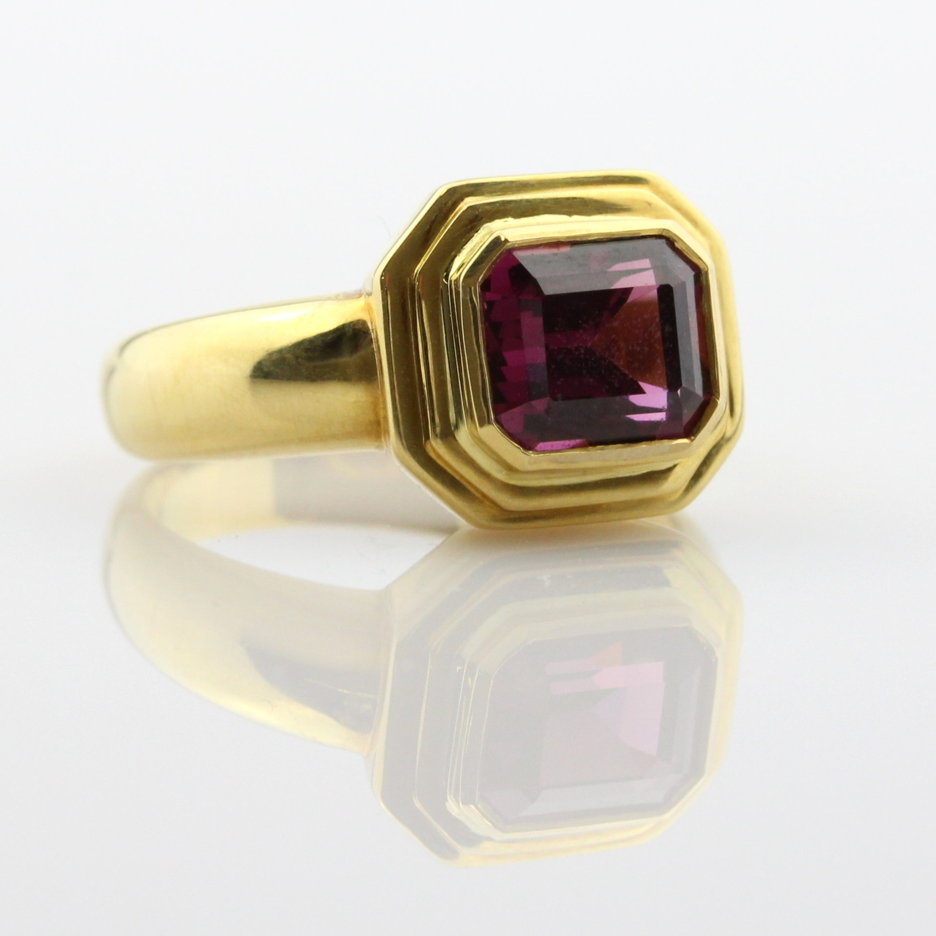 Emerald cut pink spinel bezel set in yellow gold ring.