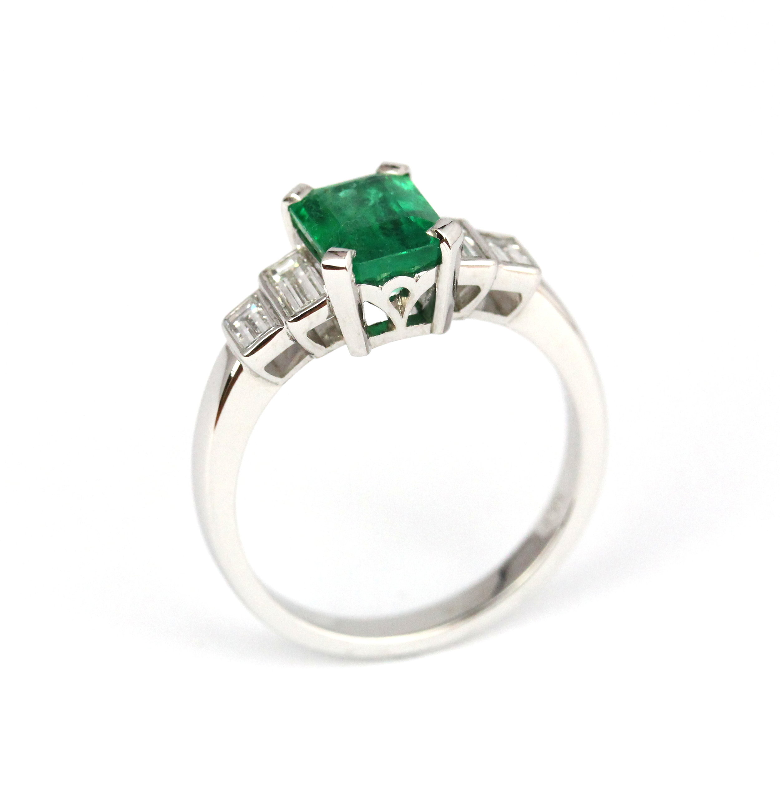 Emerald with bezel set baguette diamonds in white gold ring.