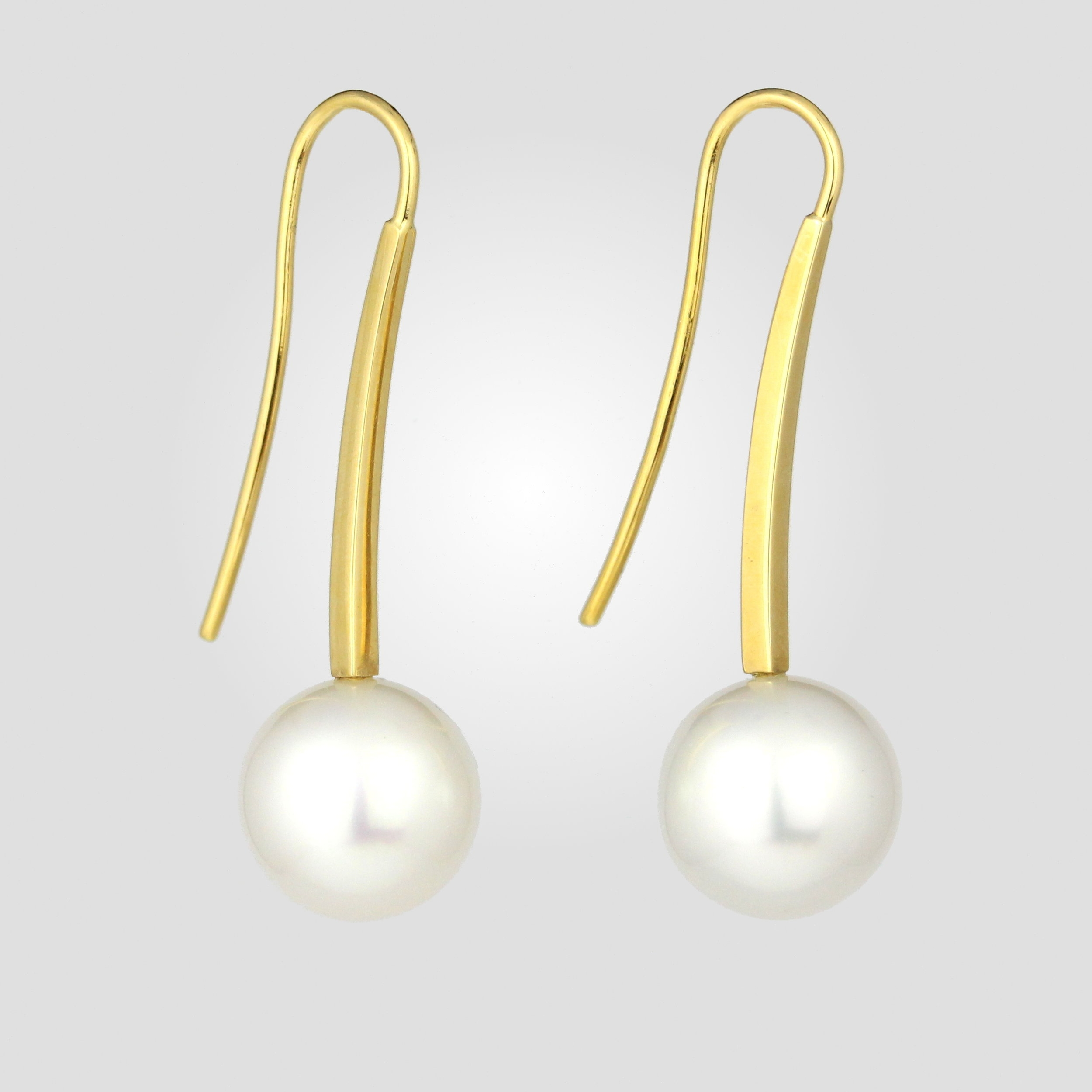 Broome pearls with long square shepherd hooks in yellow gold.