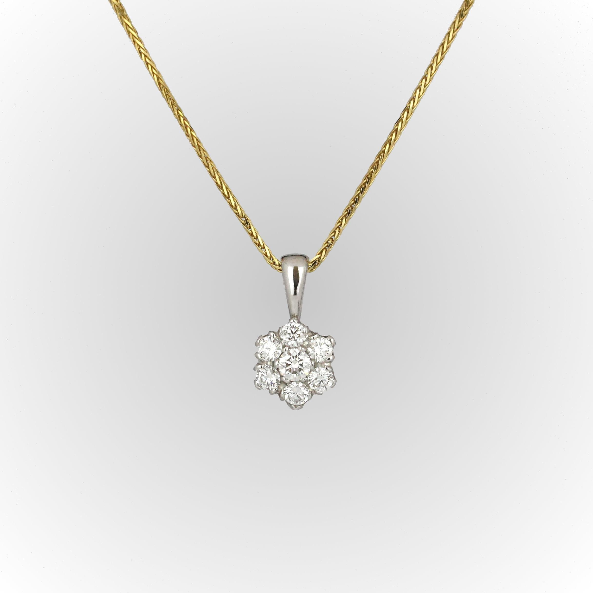 White gold diamond cluster pendant on yellow gold chain.