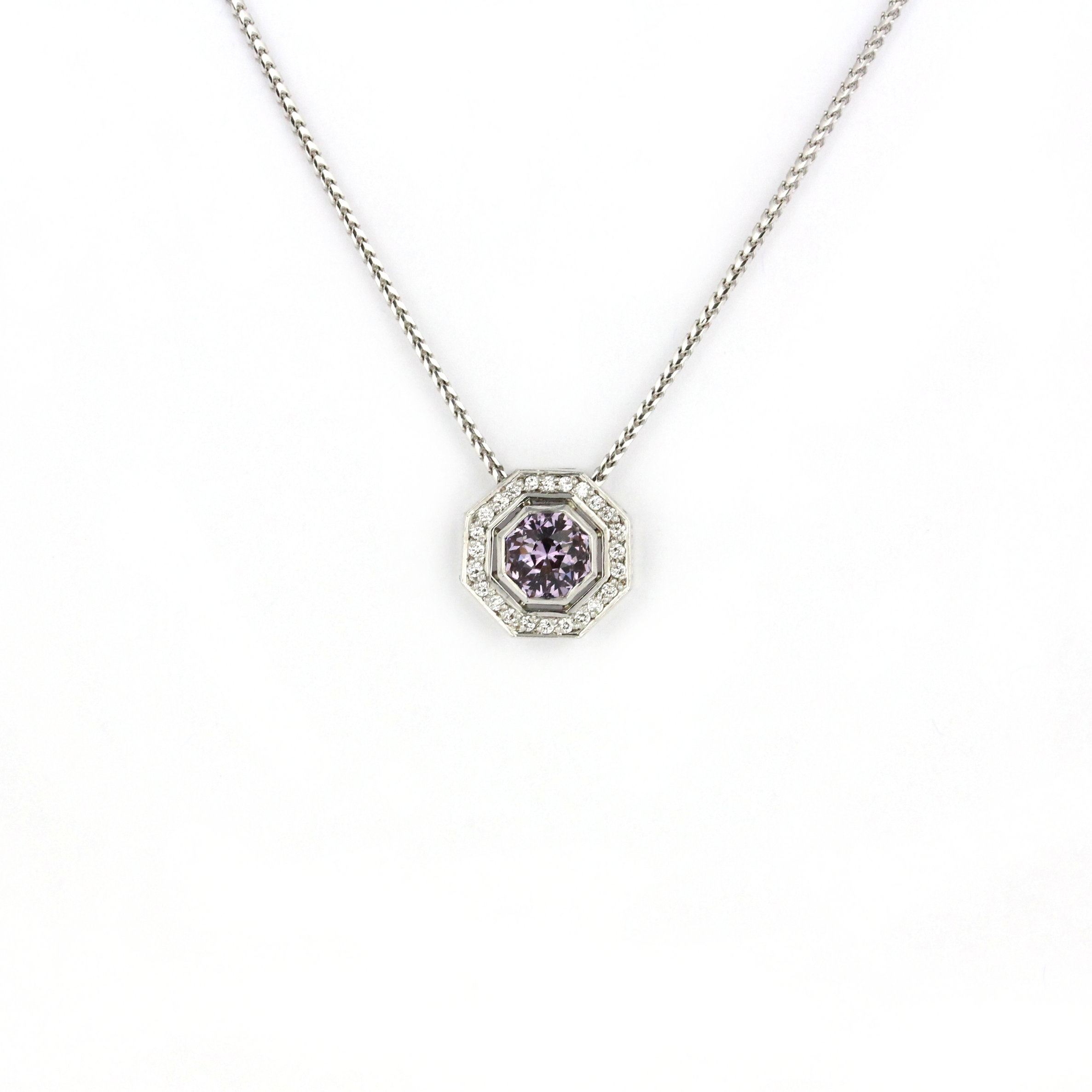 Hexagonal grey/purple spinel set in white gold surrounded by diamonds.