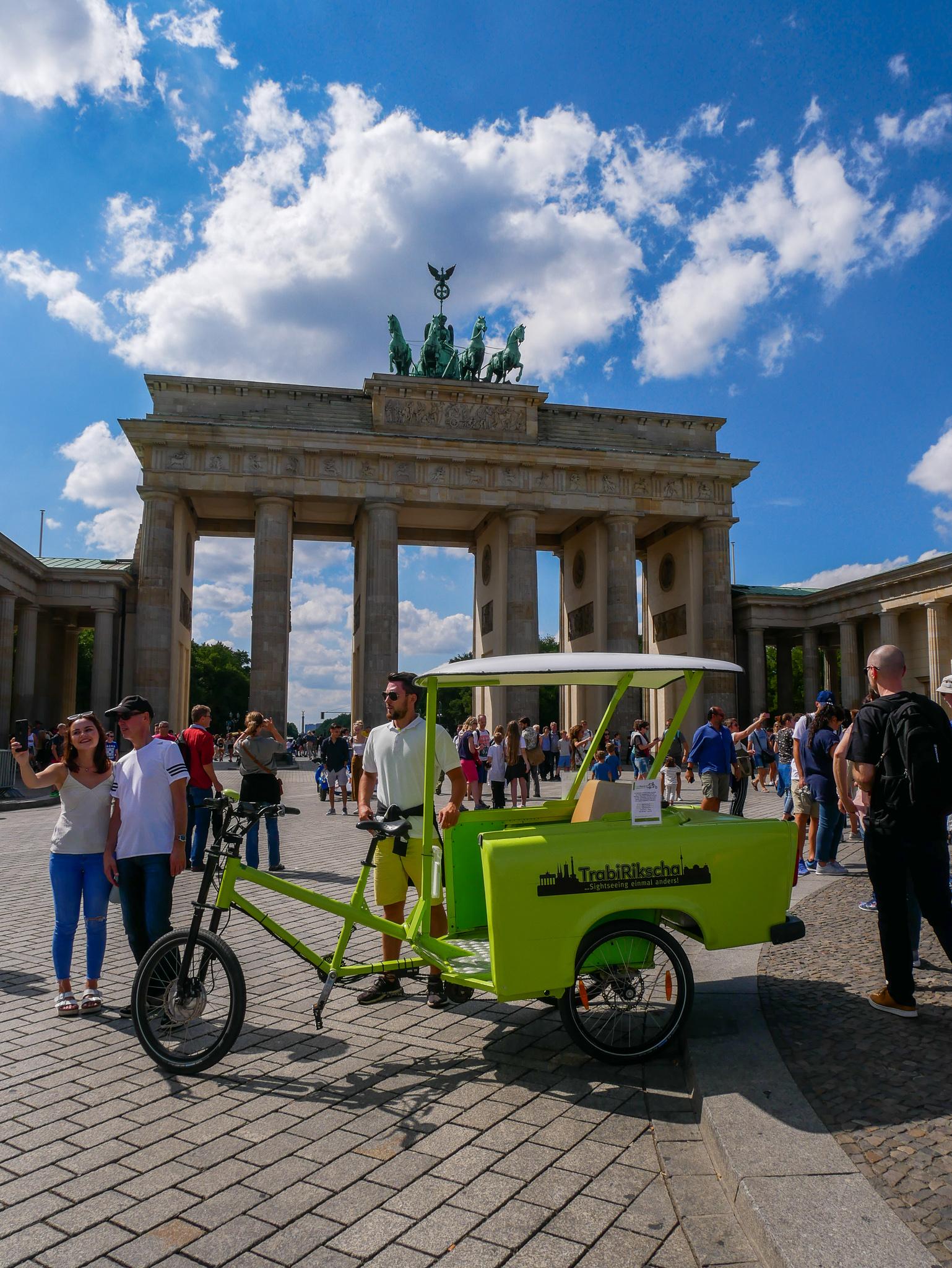 Brandenburger tor – Ett av Berlins landmärken och en gammal trabant som blivit rikscha.