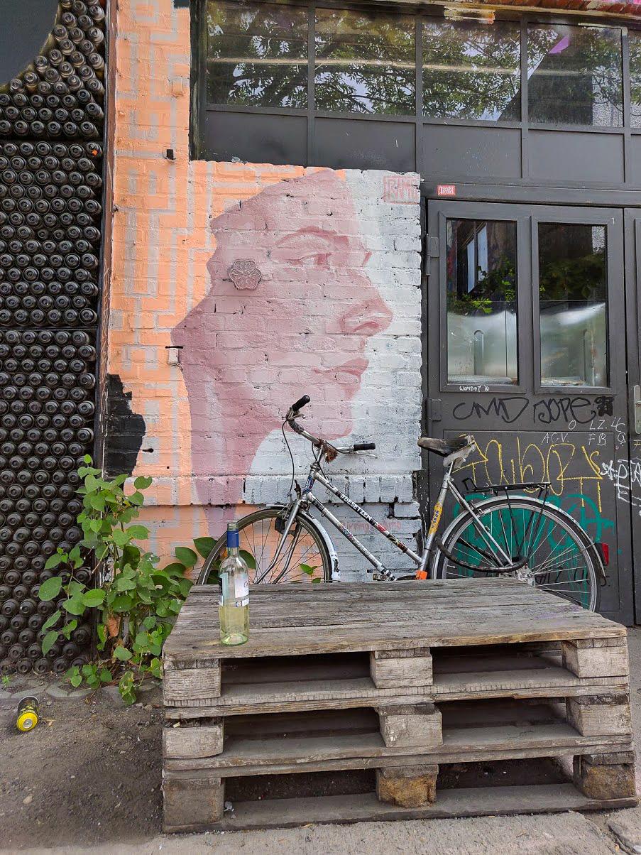 Den här bilden är en sammanfattning av Berlin: gatukonst, graffiti, en vägg gjord av gamla sprayflaskor, en sprayflaska, en lastpall, en cykel och en bortglömd vinflaska.