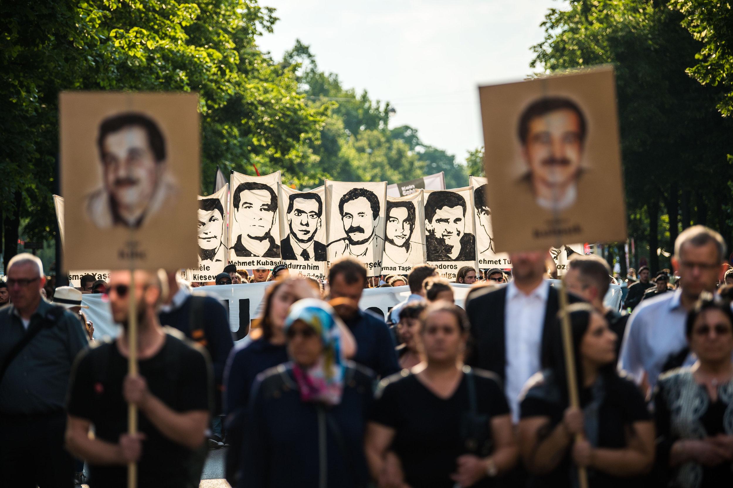 11.07.2018, Bayern, München:  Demonstranten halten bei einer Kundgebung Schilder mit Porträtabbildungen der NSU-Opfer. In München war am Morgen der Prozess gegen den rechtsterroristischen NSU mit Schuldsprüchen zu Ende gegangen. Foto: Lino Mirgeler/dpa